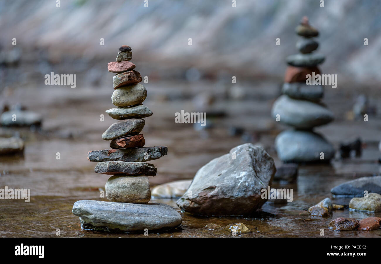 Balance and wellness concept. Close-up of river stones balanced in the shallow mountain creek. Low depth of field. Zen and spa inspired - Stock Image