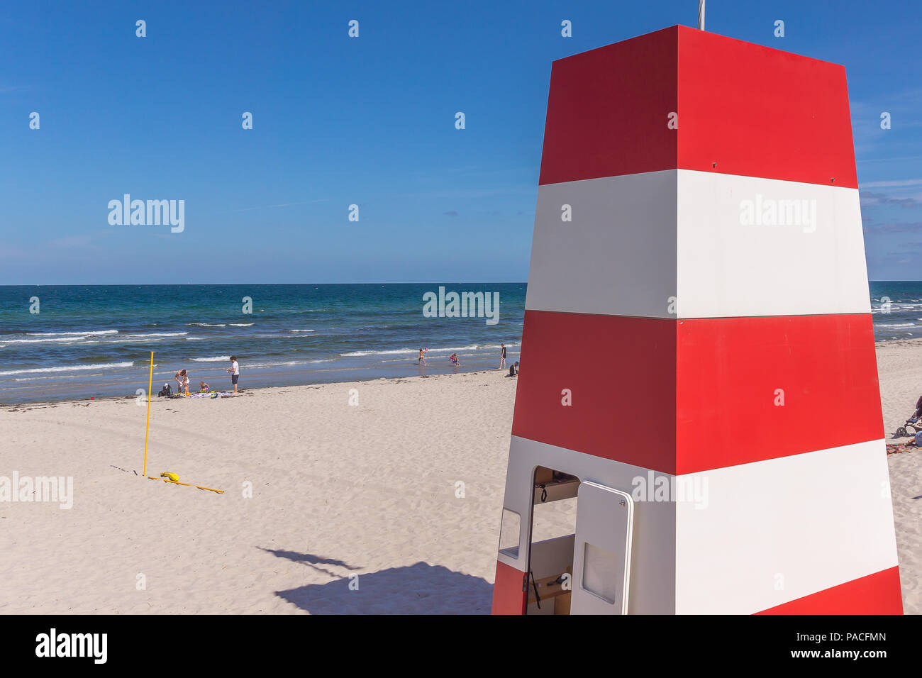 A red and white rescue tower with several stocks on the beach. Rorvig, Denmark, July 20, 2018 - Stock Image