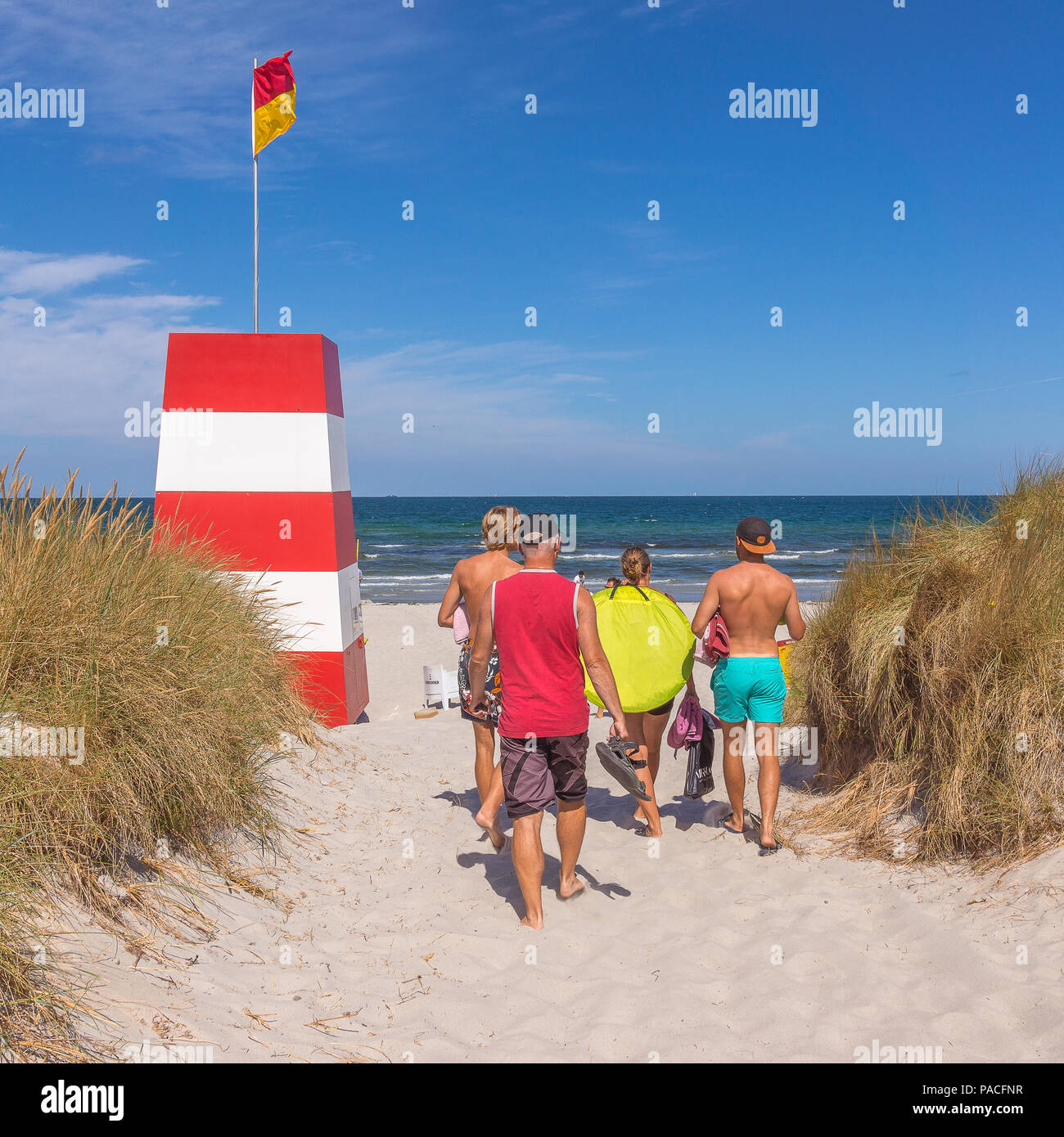 people walking in the sand towards the sea and a red an white rescuing tower, Rorvig, Denmark, July 20, 2018 - Stock Image