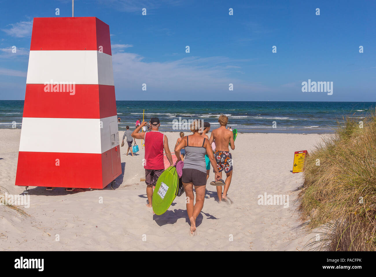 People walking in the sand towards the sea and a red an white rescue tower, Rorvig, Denmark, July 20, 2018 - Stock Image