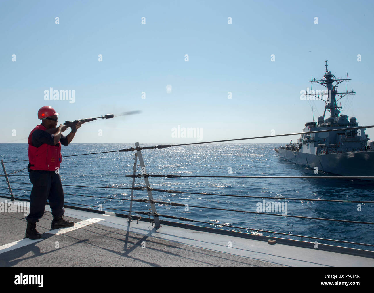 160316-N-DQ503-047 ATLANTIC OCEAN (March 16, 2016) – Gunner's Mate 3rd Class Allen Marshall, from Lawton, Okla., fires a shotline from the forecastle of the guided-missile destroyer USS Roosevelt (DDG 80) to the guided-missile destroyer USS Stout (DDG 55) during a towing exercise. Roosevelt and Stout are underway conducting Composite Training Unit Exercise (COMPTUEX) with the Dwight D. Eisenhower Carrier Strike Group in preparation for a future deployment. (U.S. Navy Photo by Mass Communication Specialist 3rd Class Taylor A. Elberg/Released) - Stock Image