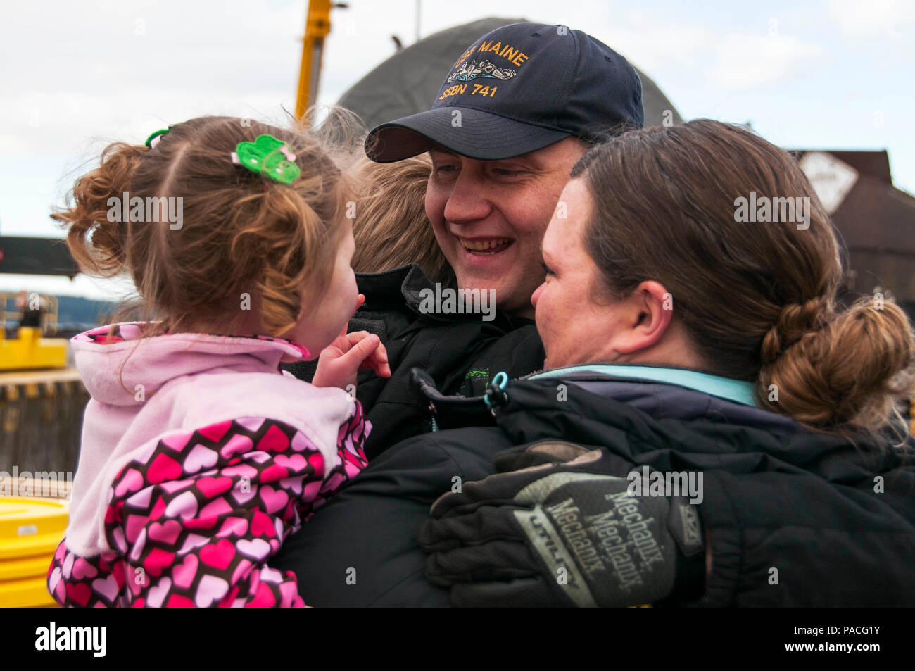 BANGOR, Wash. (March 16, 2016) – Electronics Technician (Nuclear) 2nd Class Adam Sidelinker, from Salisbury, N.C., assigned to the Blue crew of the Ohio-class ballistic-missile submarine USS Maine (SSBN 741), is welcomed home to Naval Base Kitsap-Bangor by his family following a routine strategic deterrent patrol. Maine is one of eight ballistic-missile submarines stationed at the base providing the most survivable leg of the strategic deterrence triad for the United States. (U.S. Navy photo by Mass Communication Specialist 2nd Class Amanda R. Gray/Released) - Stock Image