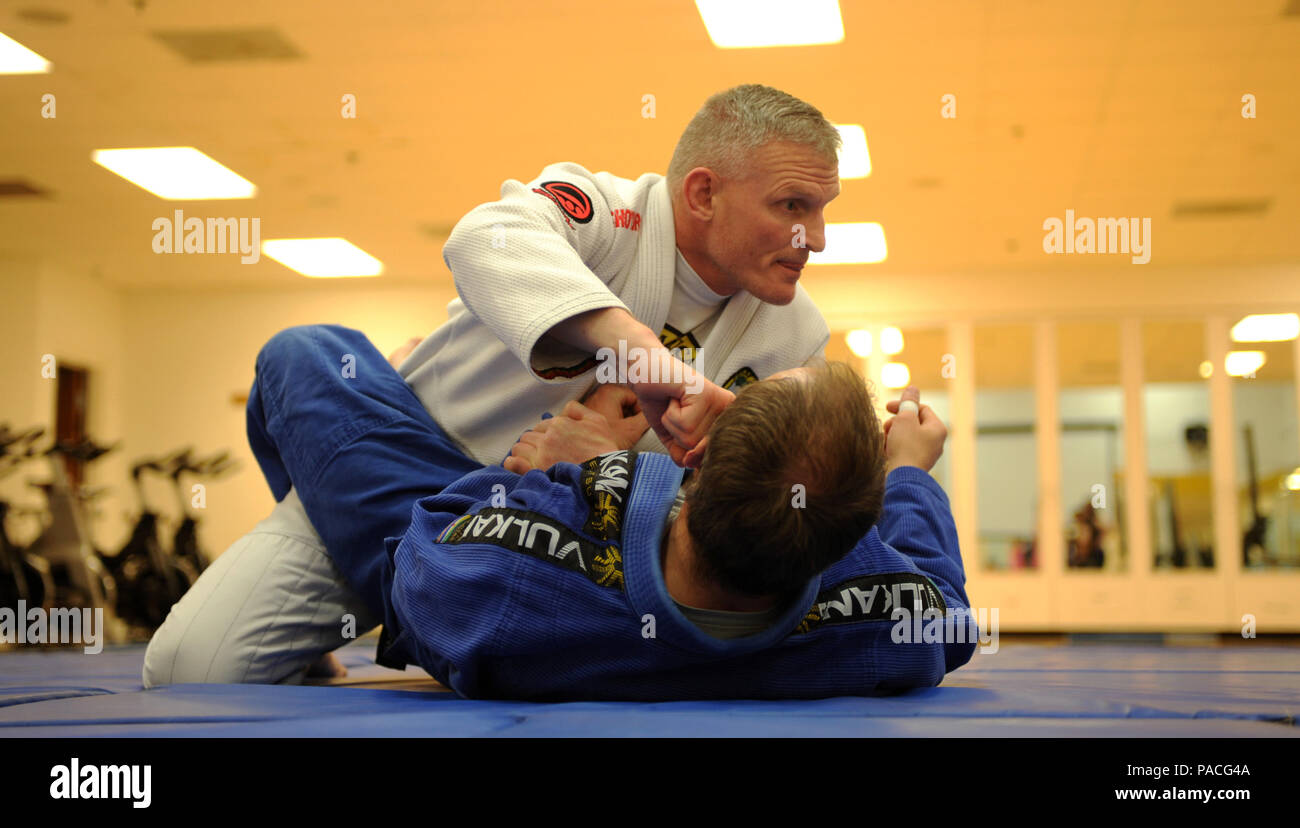 U.S. Army National Guard Sgt. 1st Class Michael Huitema, 109th Regional Support Group detachment sergeant pins Joe Reiter, Lead, S.D., paramedic, to the ground during a women's self-defense training seminar at Ellsworth Air Force Base, S.D., March 14, 2016. Brazilian jiu-jitsu is a martial art, combat sport and self-defense system that focuses on grappling and ground fighting. (U.S. Air Force photo by Airman 1st Class Denise M. Nevins/Released) - Stock Image