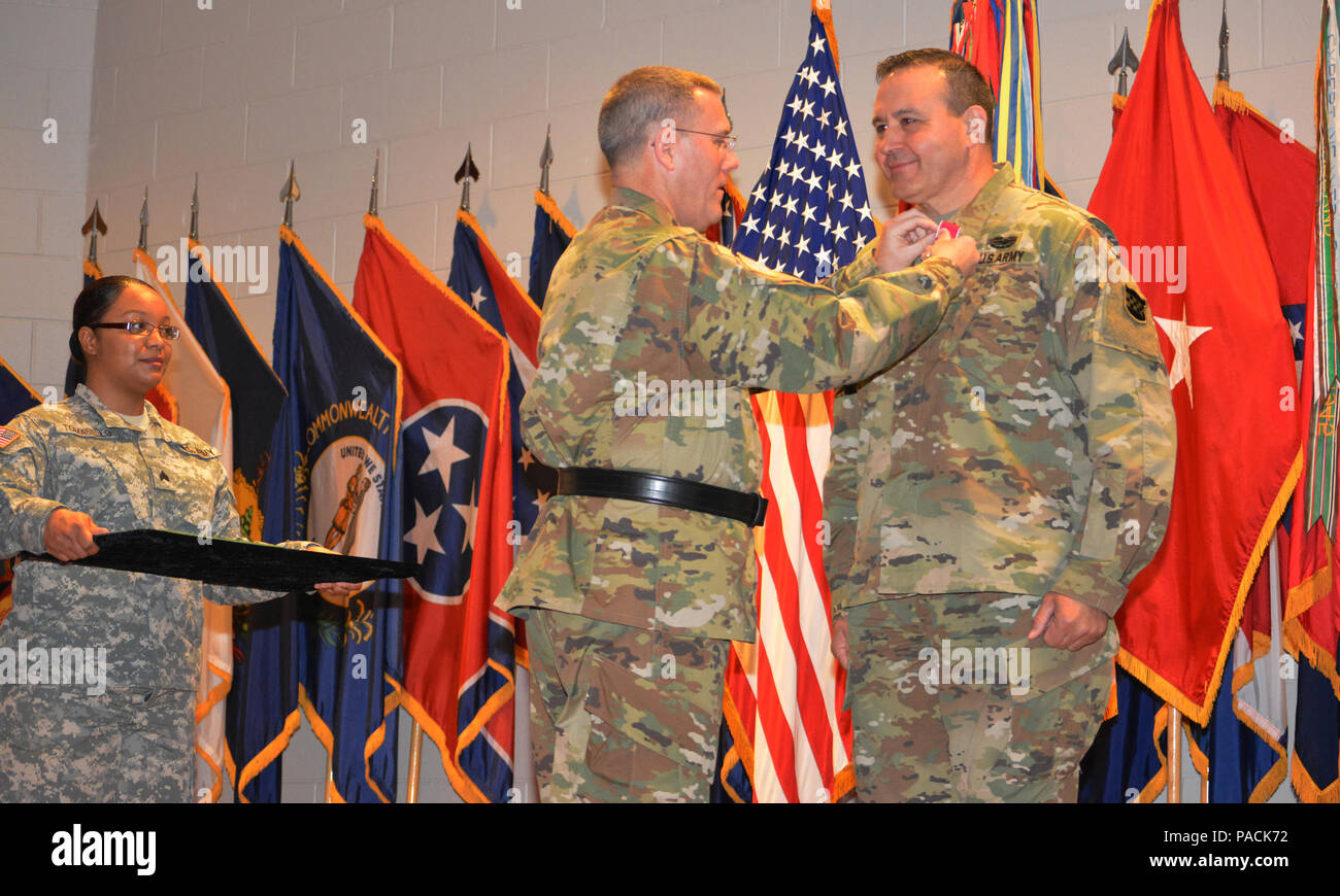 Brig. Gen. Steven W. Ainsworth, the 94th Training Division commander, awards the Legion of Merit to Command Sgt. Maj. Arlindo Almeida, the outgoing command sergeant major, for his time as the division's senior noncommissioned officer. Almeida transferred his responsibilities to Command Sgt. Maj. Sharon Campbell making her the division's first command sergeant major during a change of responsibility ceremony at Fort Lee Va., March 18, 2016. - Stock Image