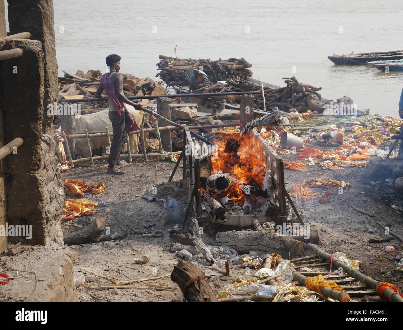 An untouchable stirs the embers of a burning body at Manakarnika Ghats, Varanasi, India. - Stock Image