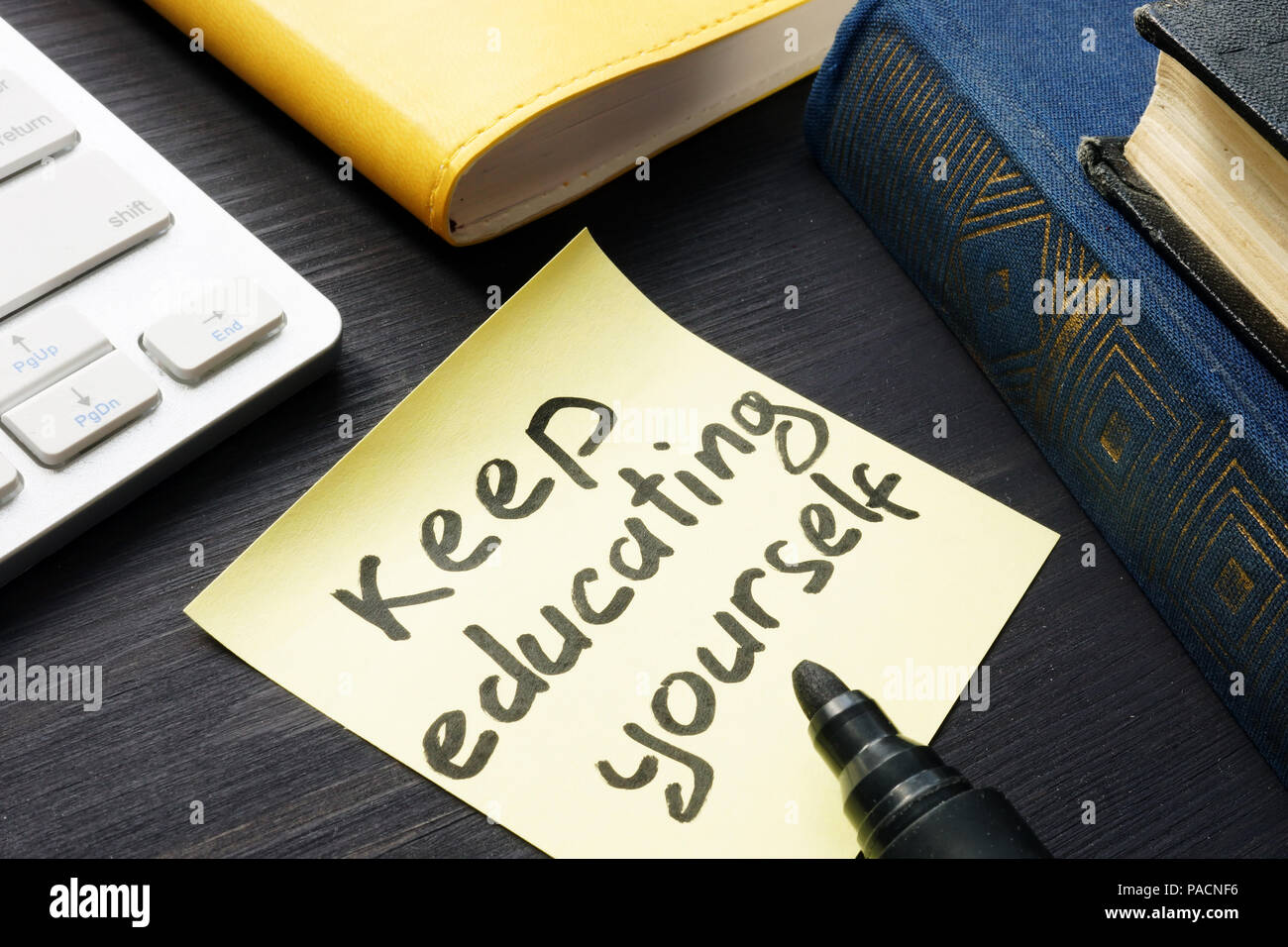 Keep educating yourself. Book and keyboard. Lifelong learning. - Stock Image