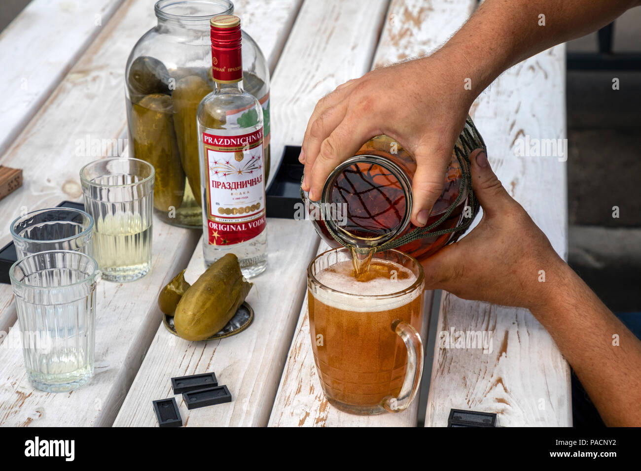 A man pours draft beer into a mug while playing dominoes in the courtyard of the house in Moscow, Russia - Stock Image