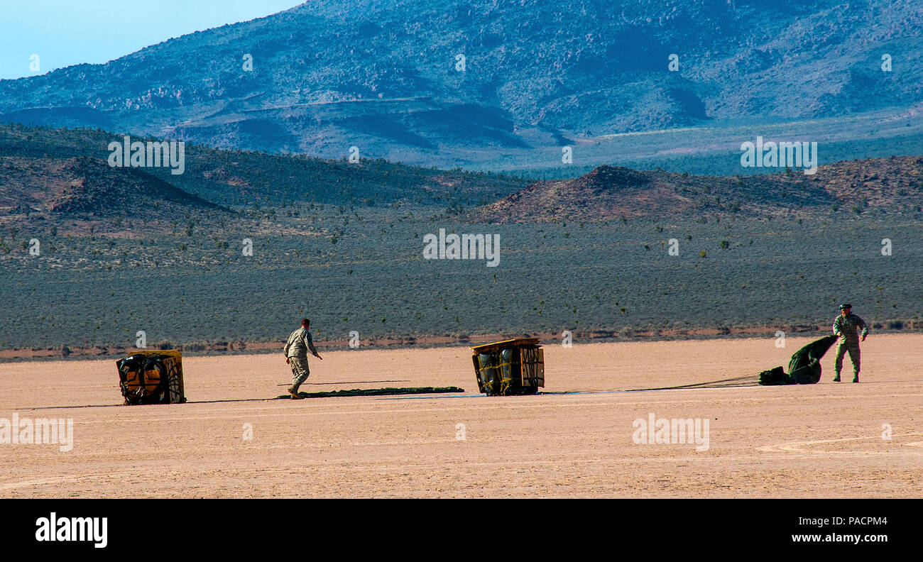 Tech Sgts. Alvin Lewis and Blane Lopez, 80th Aerial Port Squadron aerial delivery, recover cargo from an air drop on a dry lake bed during Red Flag 16-2 March 5, 2016, near Nellis Air Force Base, Nev. Capable of using unpreparedrunwaysfor takeoffs and landings, the C-130 was originally designed as a troop,medevac and cargo transport aircraft. (U.S. Air Force photo/Staff Sgt. Daniel Phelps) - Stock Image