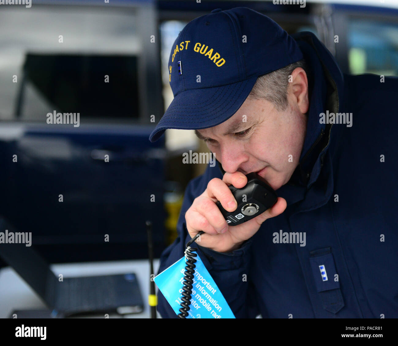 Chief Warrant Officer Michael Wood, a member of the Coast Guard 13th District response technology division, uses a mobile high frequency radio to communicate with the U.S. Customs and Border Protection National Law Enforcement Communications Service Center in Orlando, Fla., during a communications exercise at Coast Guard Base Seattle, March 22, 2016. The exercise simulated a communications blackout cased by a natural disaster. (U.S. Coast Guard photo by Petty Officer 1st Class George Degener) - Stock Image