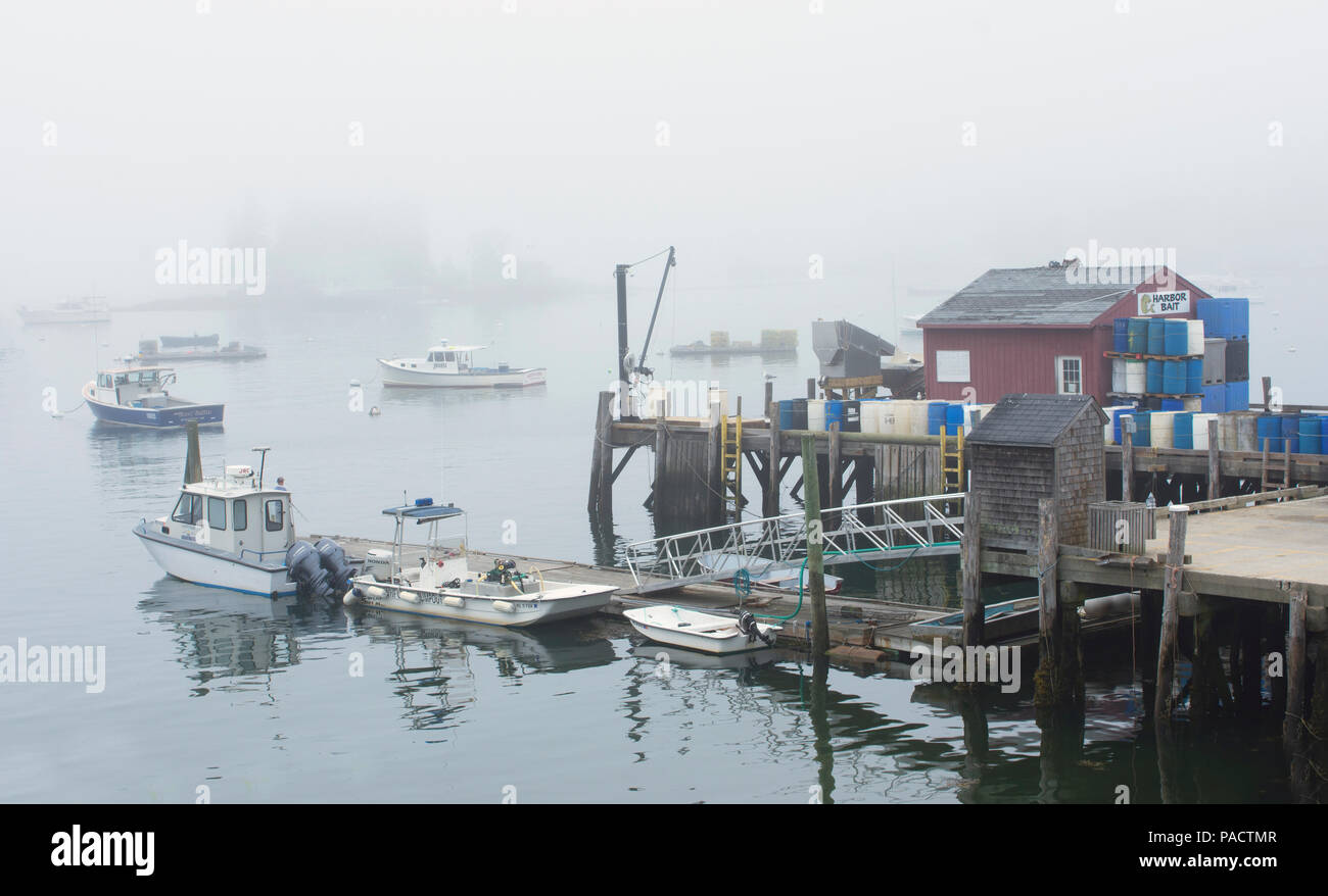 A commercial dock and boats in Boothbay Harbor, Maine, USA on a foggy afternoon. - Stock Image