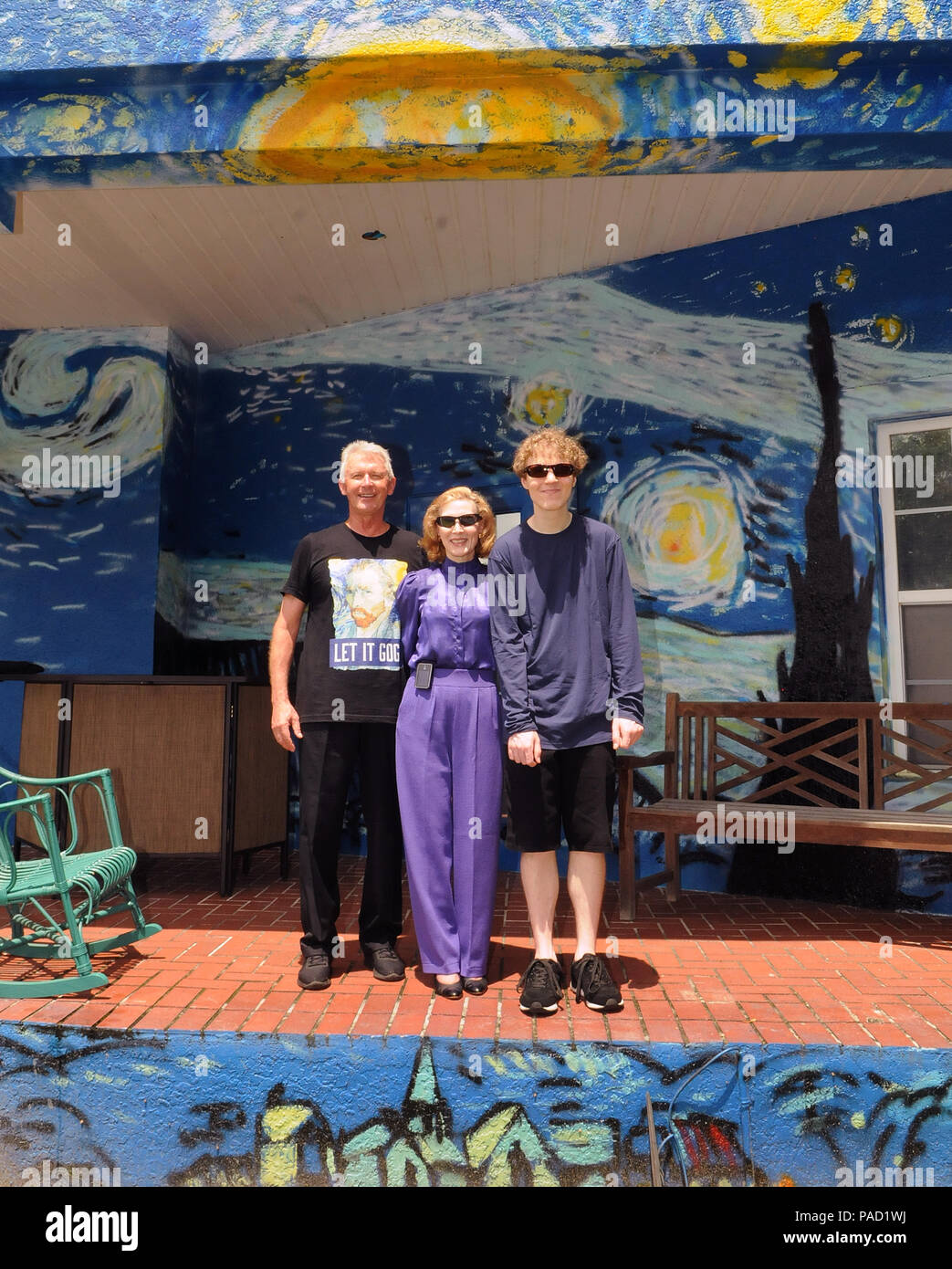 Florida, USA. 21 July 2018. Lubomir Jastrzebski (left), his wife, Nancy Nemhauser, and their son, Chip (right), pose in front of their mural-painted home on July 21, 2018 in Mount Dora, Florida. On July 17, 2018, the couple won a one year battle with the Mount Dora City Council to keep the van Gogh inspired art work on their wall and home. The code enforcement dispute began when the homeowners hired an artist to paint a wall outside their home in the likeness of van Gogh's painting 'The Starry Night' as a means to calm their 25 year-old son who is autistic and loves va - Stock Image