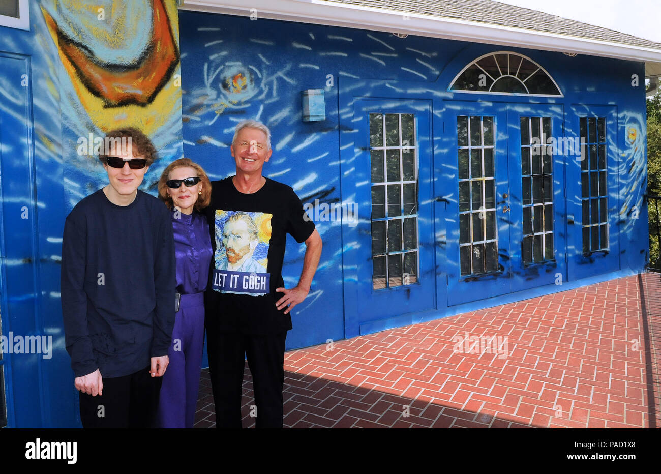 Florida, USA. 21 July 2018. Lubomir Jastrzebski (right), his wife, Nancy Nemhauser, and their son, Chip (left), pose in front of their mural-painted home on July 21, 2018 in Mount Dora, Florida. On July 17, 2018, the couple won a one year battle with the Mount Dora City Council to keep the van Gogh inspired art work on their wall and home. The code enforcement dispute began when the homeowners hired an artist to paint a wall outside their home in the likeness of van Gogh's painting 'The Starry Night' as a means to calm their 25 year-old son who is autistic and loves va - Stock Image