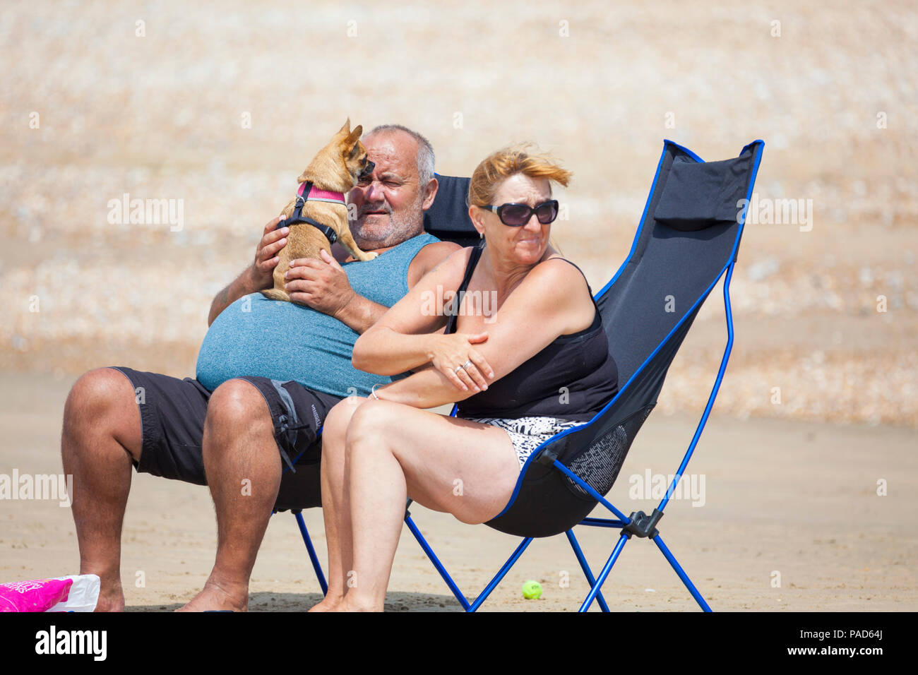 Camber Sands, East Sussex, UK. 22nd Jul, 2018. UK Weather: Hot and sunny weather in camber with scores of people hitting the beach early as this is predicted to be another scorcher of a day. Temperatures are expected to exceed 25°C. Pictured is a man in a deckchair with dog in his lap licking his face. Photo Credit: Paul Lawrenson / Alamy Live News - Stock Image