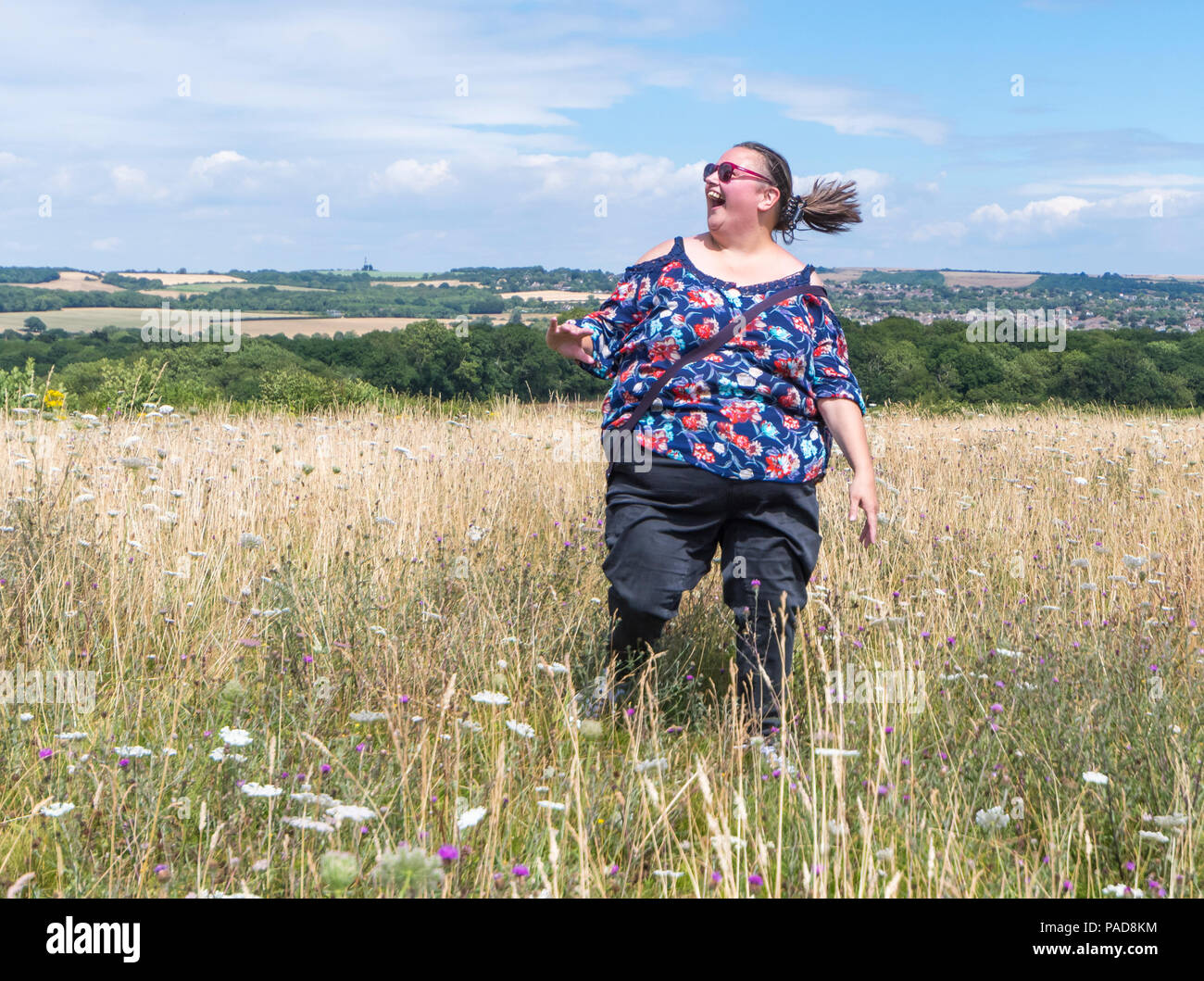 Young woman jumps and runs around a meadow in the British countryside on a hot day in the July 2018 heatwave at Highdown Hill, West Sussex, England, UK. Happiness concept. Being happy concept. Jumping with joy concept. - Stock Image
