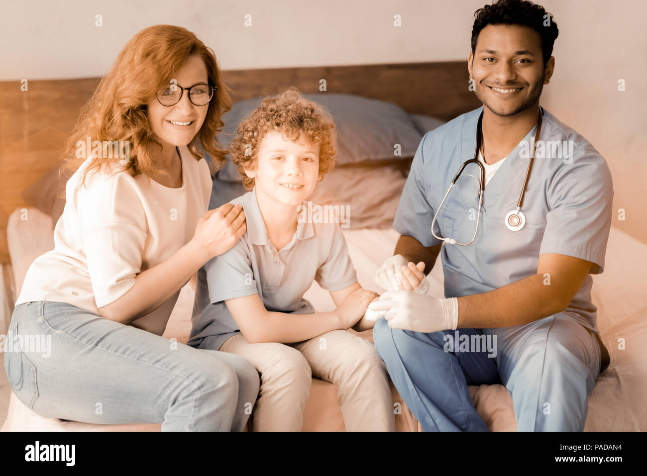 Delighted boy sitting between his doc and mom Stock Photo