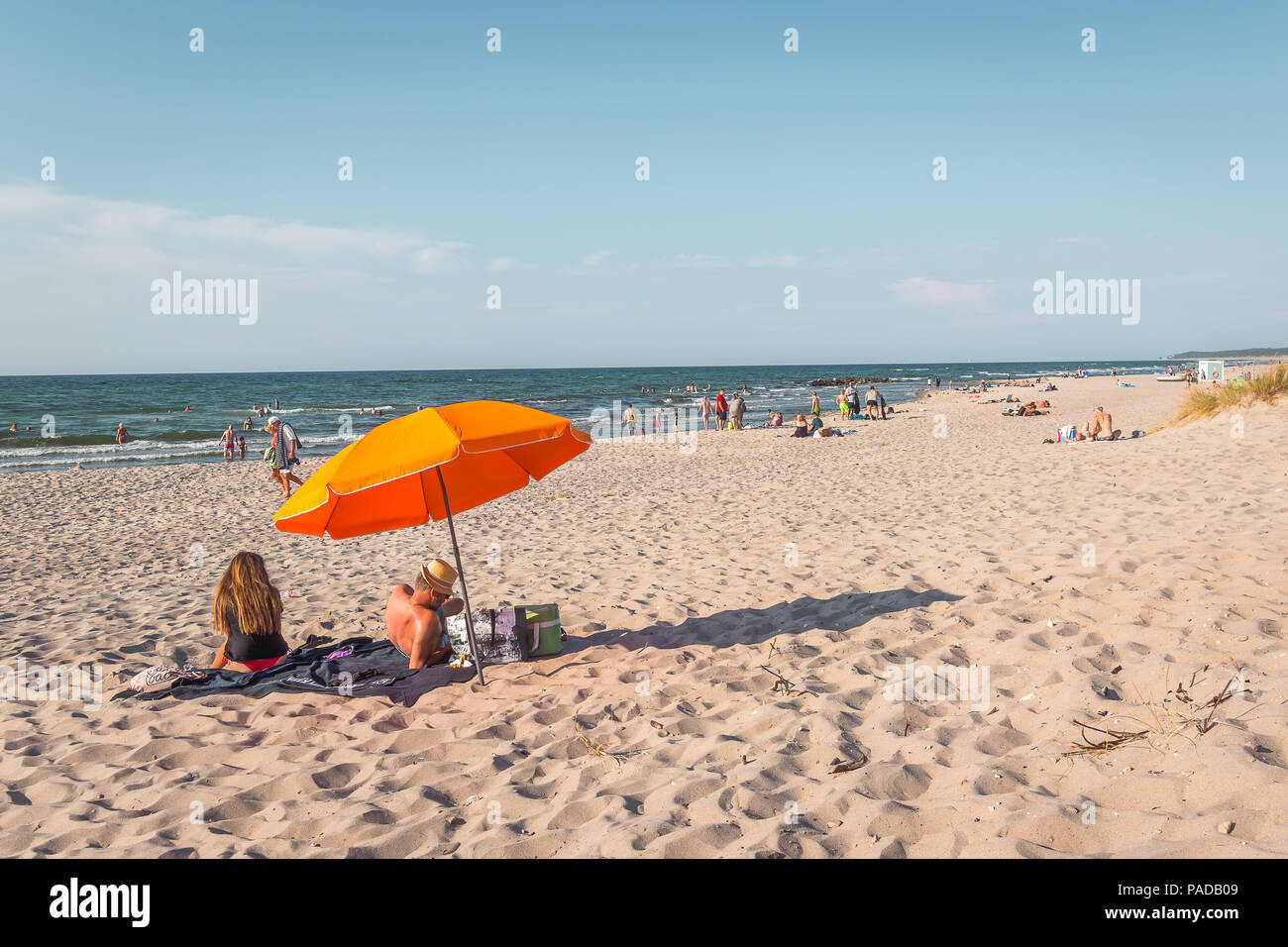Man and woman sitting on a blanket under an orange umbrella on the beach in the afternoon sunshine, Rorvig, Denmark, July 16, 2018 - Stock Image