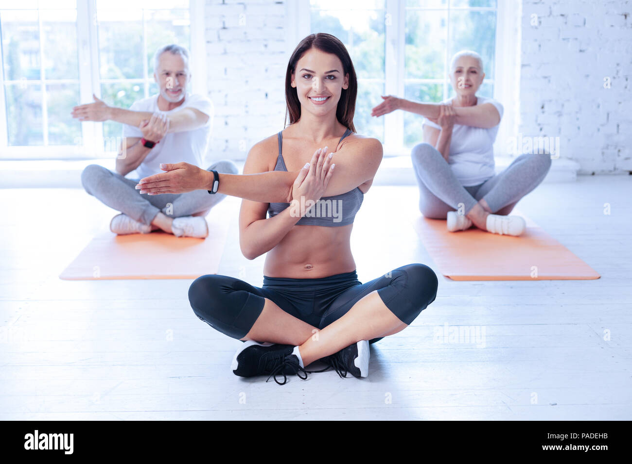 Happy yoga tutor training with her clients - Stock Image