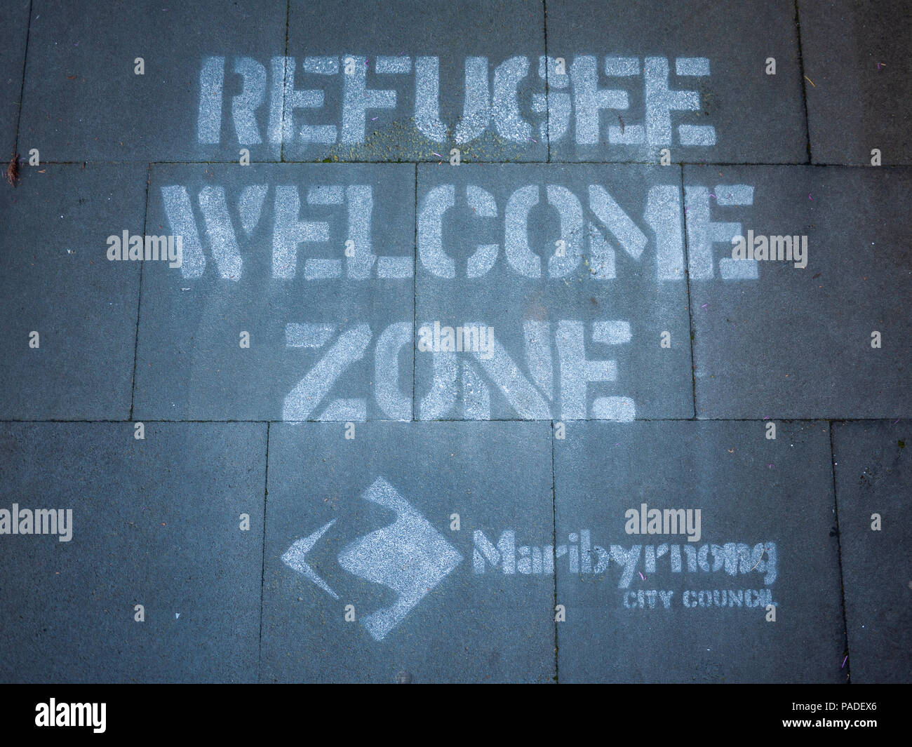 Text on footpath says 'Refugee Welcome Zone' at front of office building of Maribyrnong City Council. Melbourne, VIC Australia - Stock Image