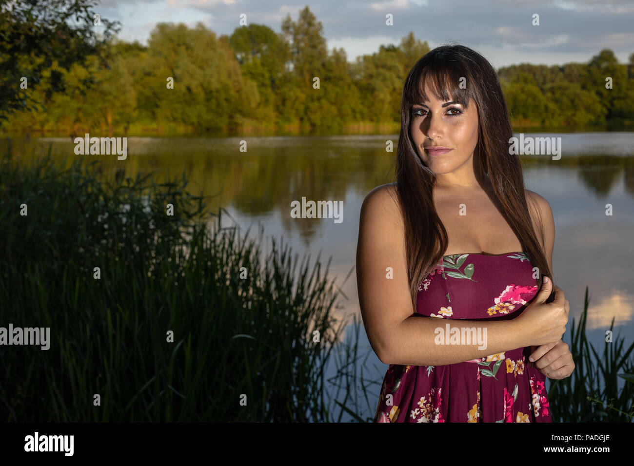 Spanish American female standing at the edge of a lake in Cambridgeshire.  Wearing a plum coloured floral dress during a summer sunset. - Stock Image