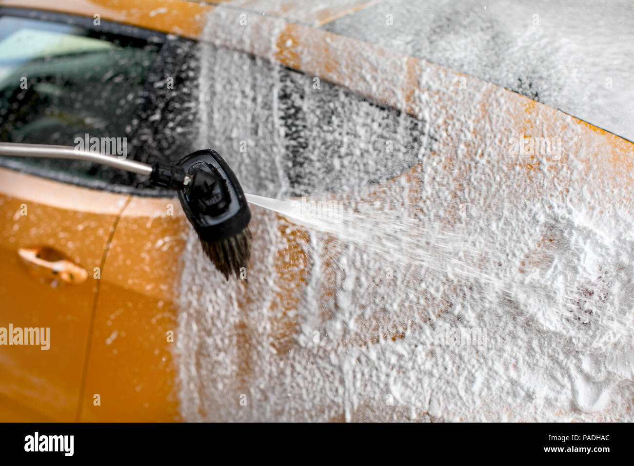 Shampoo and foam being sprayed on yellow car side, cleaned at carwash. Stock Photo