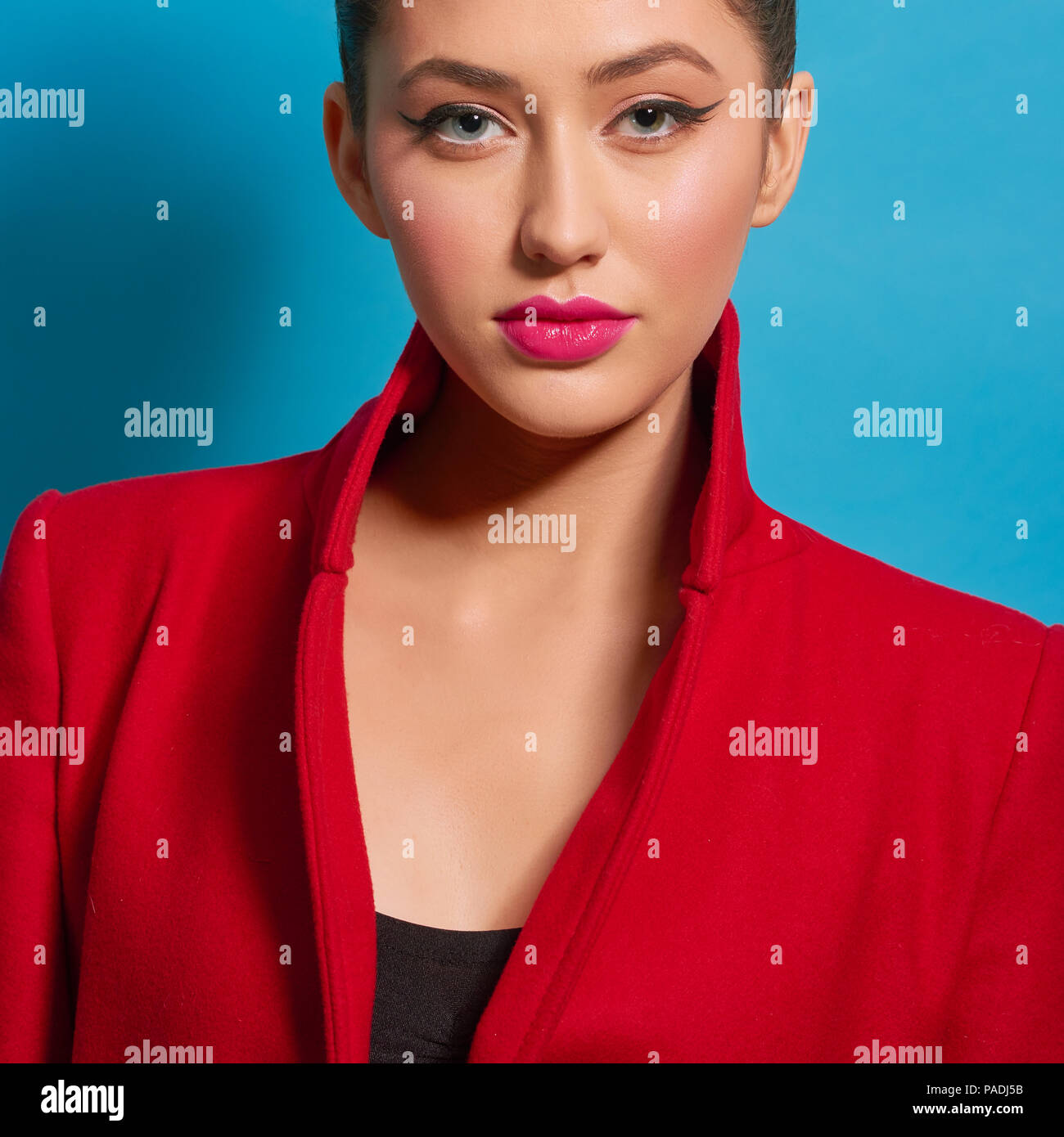 Contrast portrait of beatiful girl wearing red coat bright make up. Pink plump lips, pale cheeks, perfect eyebrow shape, big eyes, healthy skin color.Looking at camera, feeling confident. - Stock Image