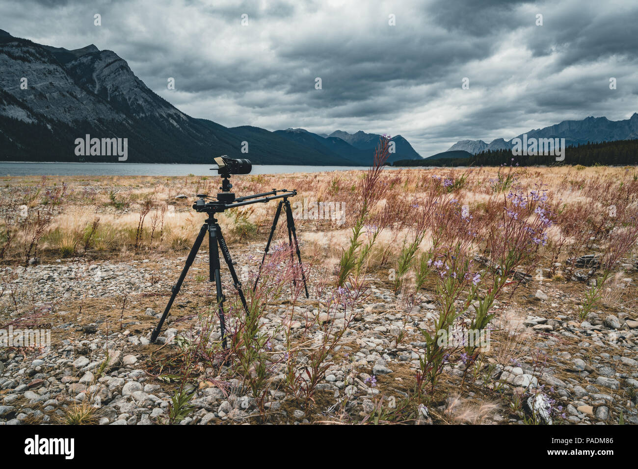 Timelapse slider setup with campera tripod across Isolated Peak and surrounding mountains and forests in Banff National Park in the Rocky Mountains in Alberta, Canada. - Stock Image