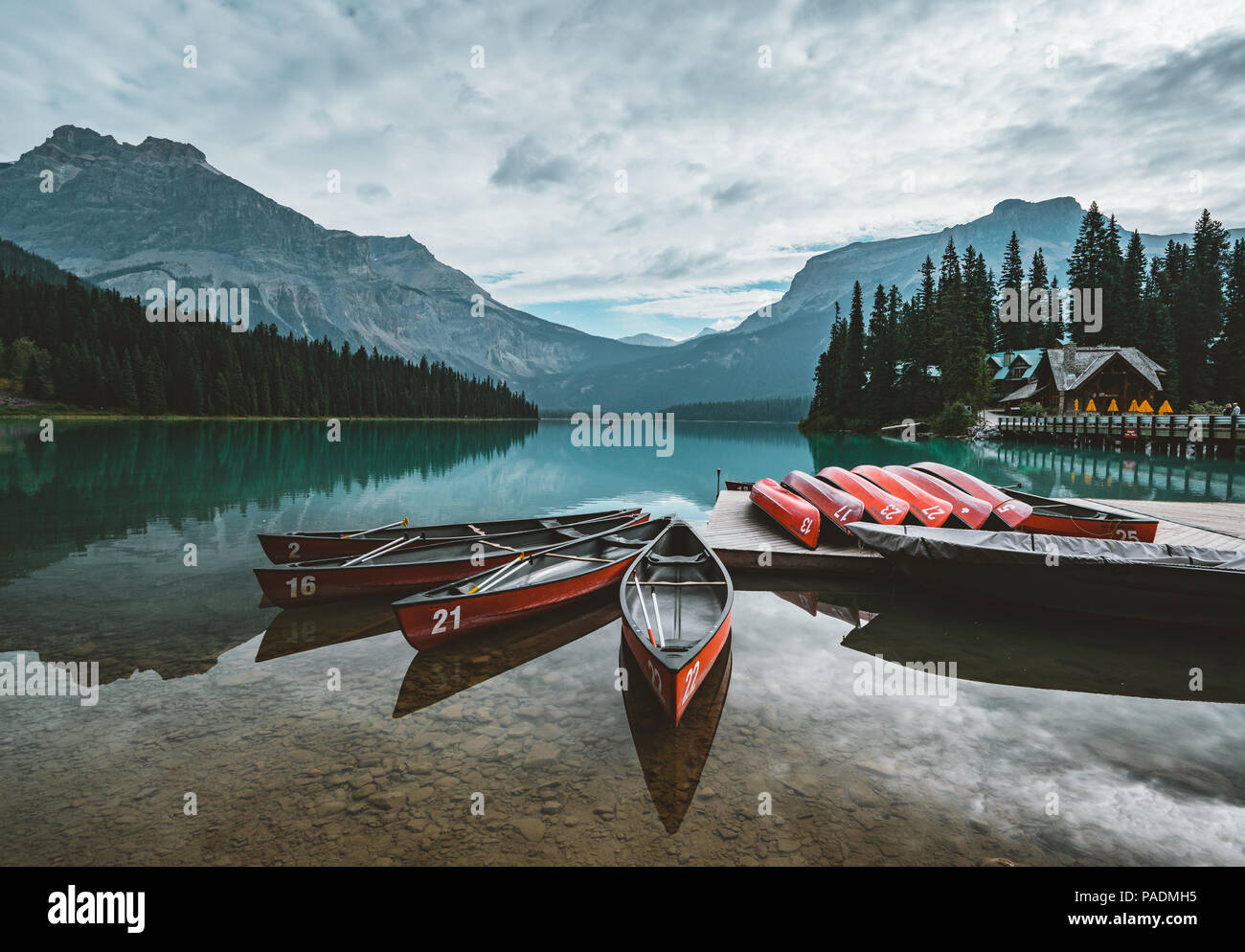 Red kayaks dry upside down. Emerald Lake in Canadian Rockies with mountains and trees and refelction. Concept of active vacation and tourism - Stock Image