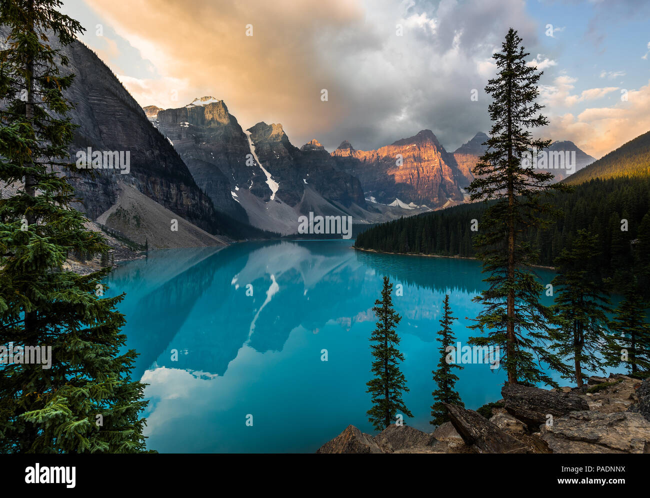 Sunrise with turquoise waters of the Moraine lake with sin lit rocky mountains in Banff National Park of Canada in Valley of the ten peaks. - Stock Image