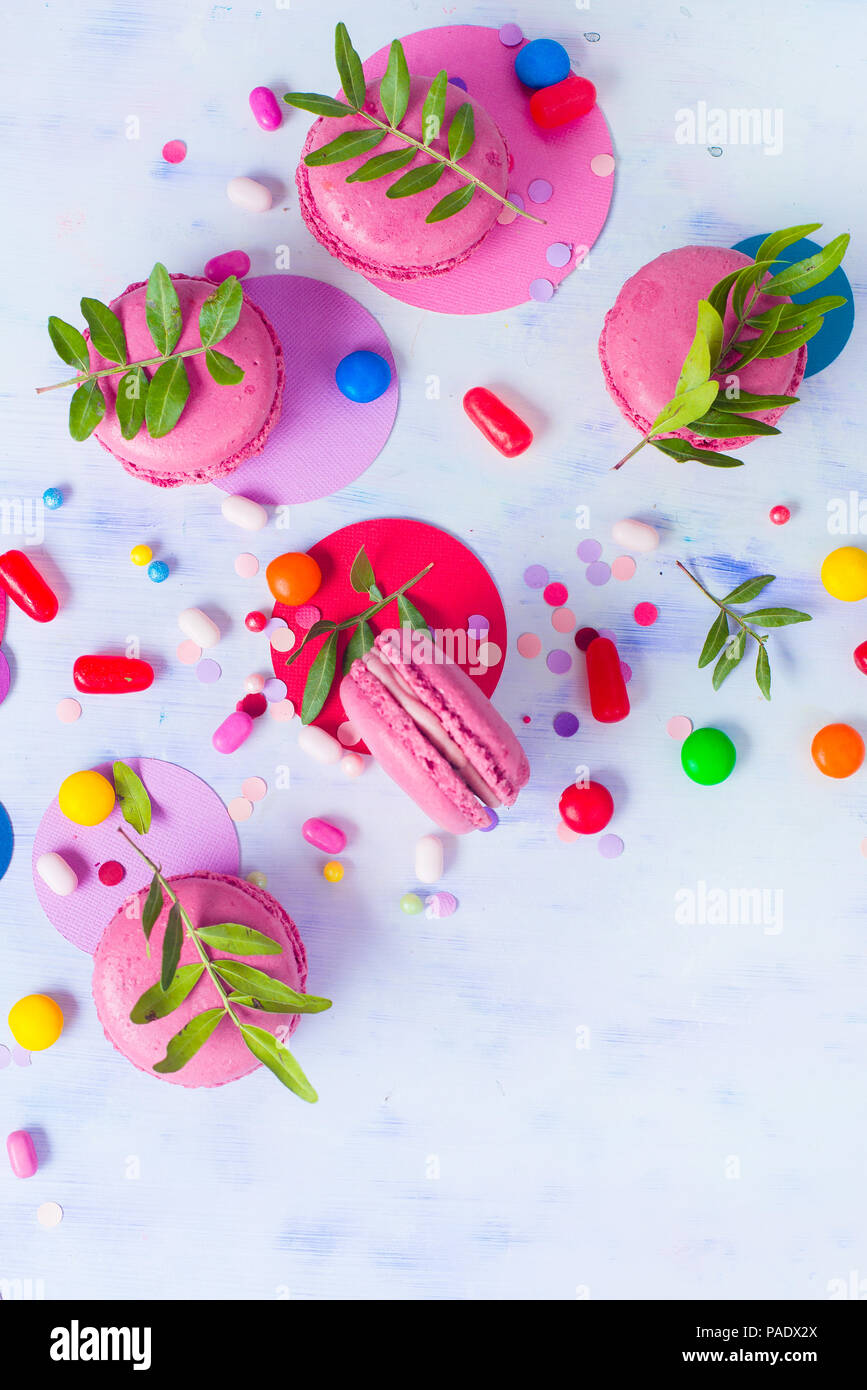 Macaroon cookies on a colorful background with confetti. Vibrant party concept with copy space. Pink and purple palette flat lay. - Stock Image