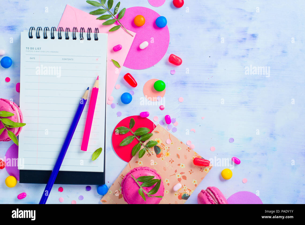 Party planning concept. Background with confetti, notepads, stationery, candies and macaroon cookies. Colorful objects flat lay in high key with copy space. - Stock Image