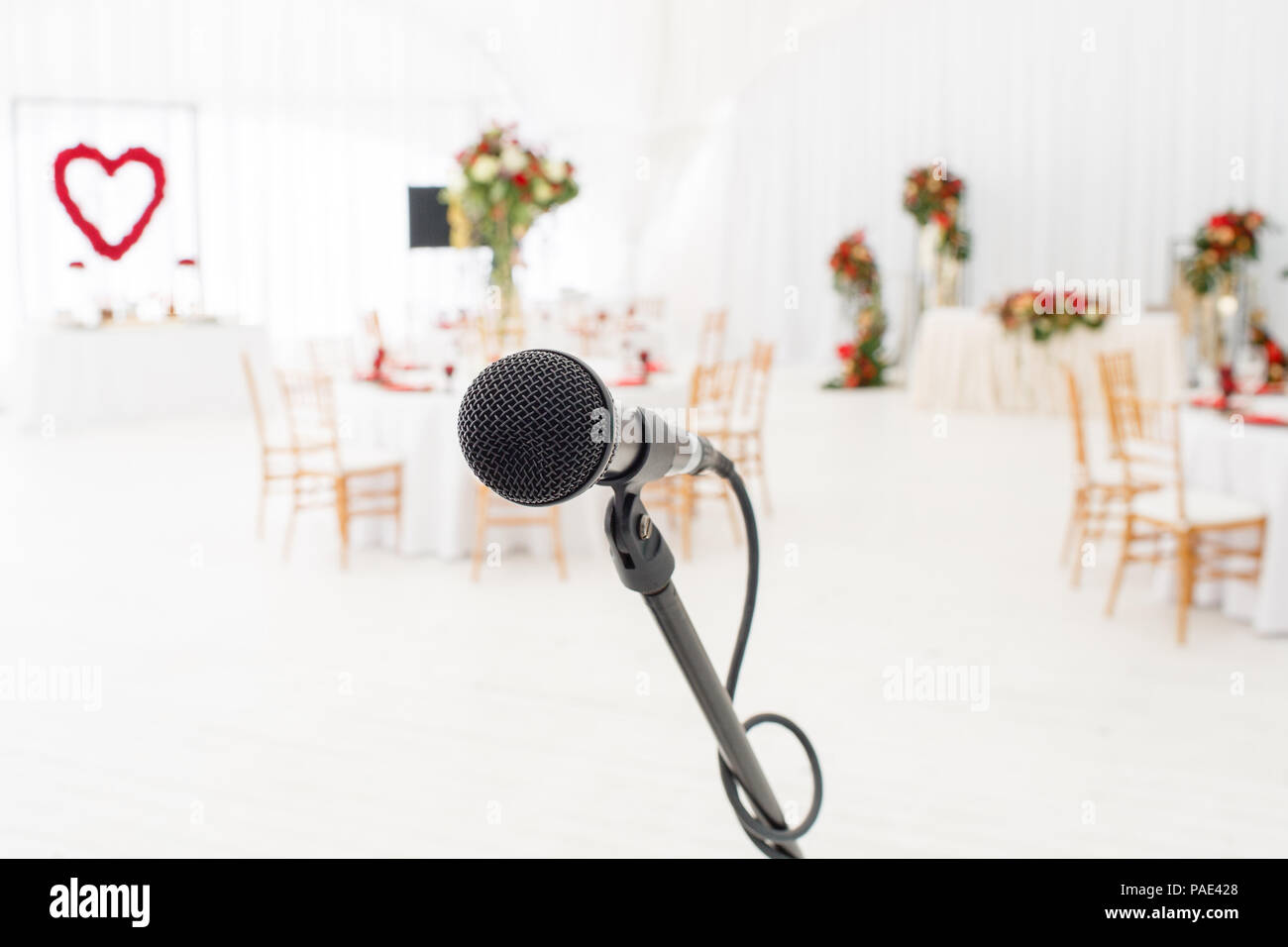 dc76778d6acc5 Microphone close-up. Focus on mic. Abstract blurred conference hall or  wedding banquet