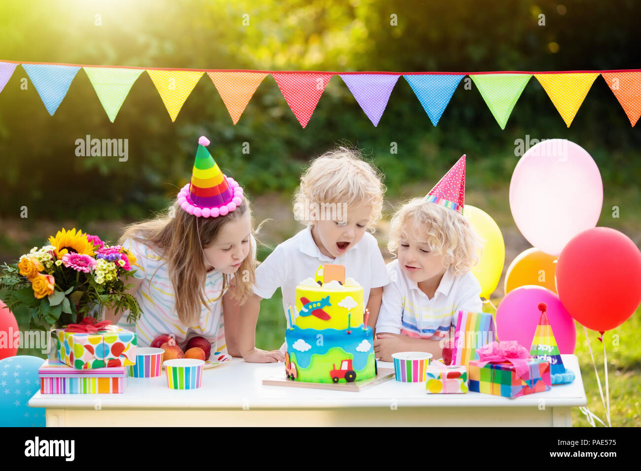 Children Blow Candles On Birthday Cake Kids Party