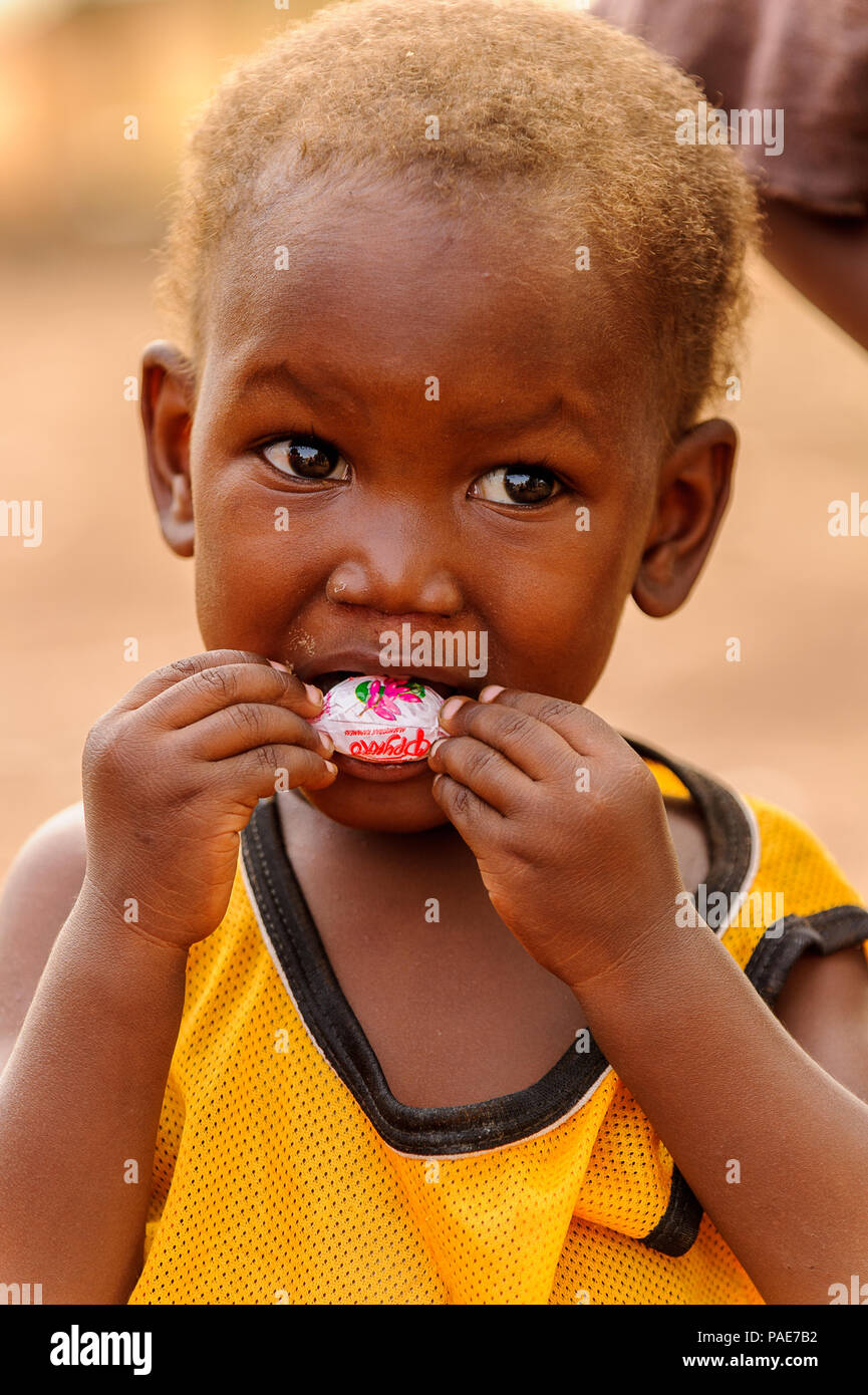 ACCRA, GHANA - MARCH 6, 2012: Unidentified Ghanaian boy eats a candy in the street in Ghana. Children of Ghana suffer of poverty due to the unstable e - Stock Image