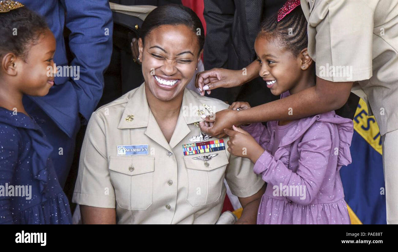CITY, N.Y. (Sept. 15, 2017) Chief Navy Counselor Danielle Marbley reacts as her daughters help pin anchors to her uniform, signifying her advancement to the rank of chief petty officer, during a ceremony at the Cradle of Aviation Museum in Garden City, N.Y. - Stock Image