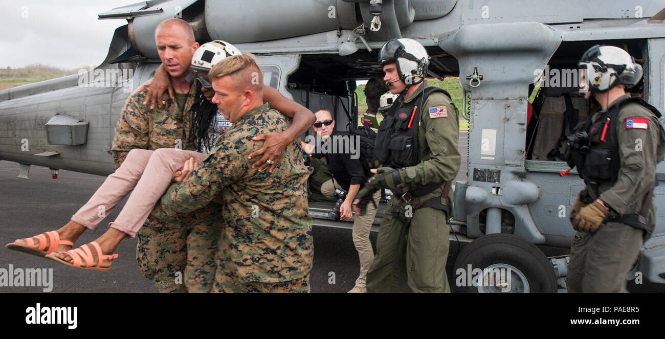 DOMINICA (Sept. 27, 2017) Sailors assigned to the amphibious assault ship USS Wasp (LHD 1) and U.S. Marines assigned to Special Purpose Marine Air Ground Task Force- Southern Command (SP MAGTAF-SC) provide aid to an evacuee as part of first response efforts to Dominica in the wake of Hurricane Maria. Evacuees are being transported to island airports for transfer to the islands of Martinique and Guadeloupe. The Department of Defense is supporting the United States Agency for International Development (USAID), the lead federal agency, in helping those affected by Hurricane Maria to minimize suff - Stock Image