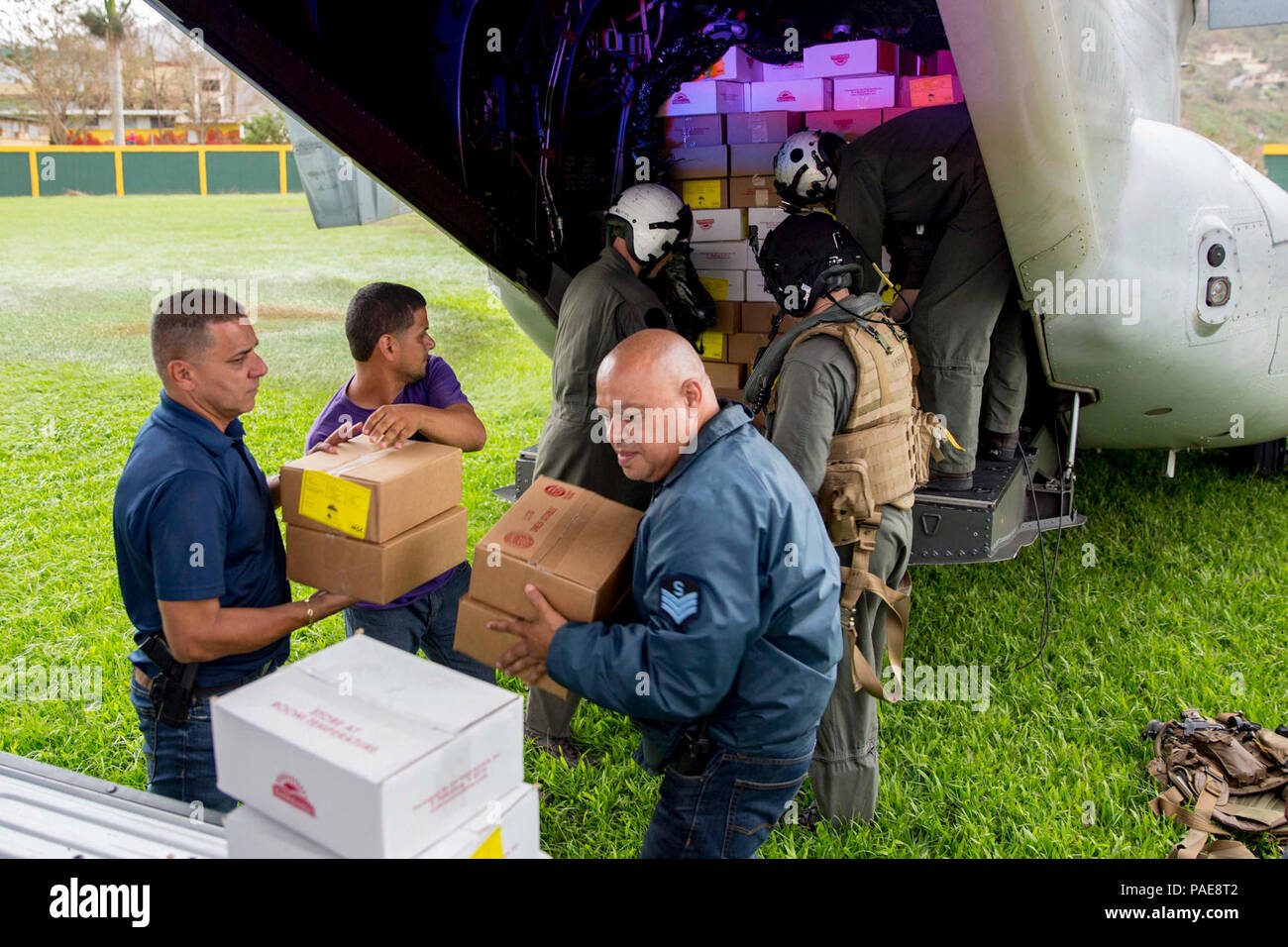 JAYUYA, Puerto Rico (Sept. 27, 2017) Marines assigned to Marine Medium Tiltrotor Squadron 162, embarked aboard the amphibious assault ship USS Kearsarge (LHD 3), and local volunteers unload food from an MV-22 Osprey in Jayuya, Puerto Rico. Kearsarge is assisting with relief efforts in the aftermath of Hurricane Maria. The Department of Defense is supporting the Federal Emergency Management Agency, the lead federal agency, in helping those affected by Hurricane Maria to minimize suffering and is one component of the overall whole-of-government response effort. - Stock Image