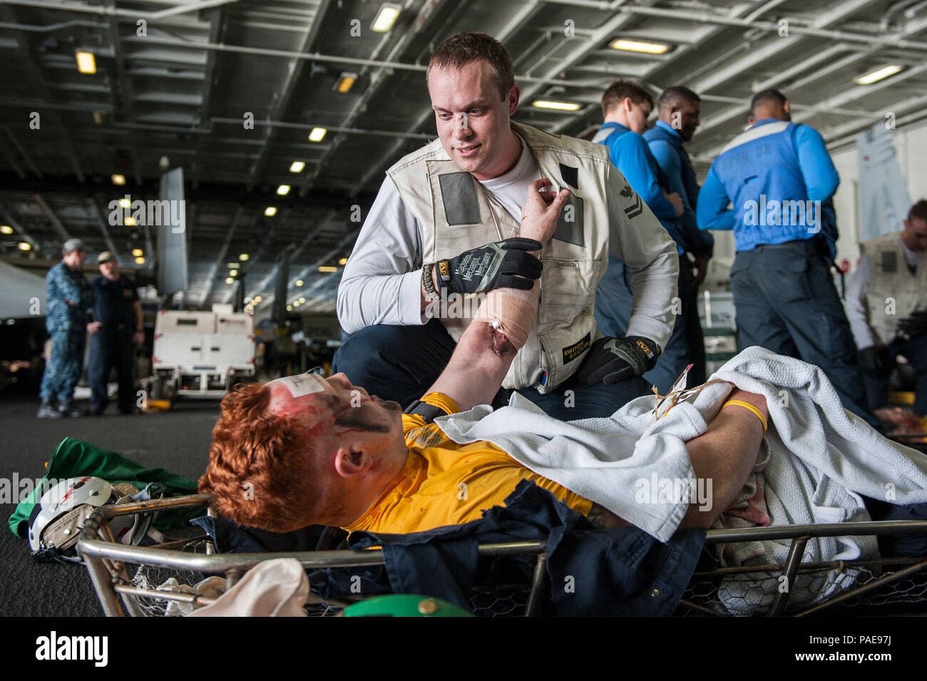 160318-N-GK939-104   ARABIAN GULF (March 18, 2016) Hospital Corpsman 2nd Class Lucas Roberts simulates maintaining a distressed casualty during a mass casualty drill in the hangar bay of aircraft carrier USS Harry S. Truman (CVN 75). Harry S. Truman Carrier Strike Group is deployed in support of Operation Inherent Resolve, maritime security operations, and theater security cooperation efforts in the U.S. 5th Fleet area of operations. (U.S. Navy photo by Mass Communication Specialist Seaman Lindsay A. Preston/Released) - Stock Image