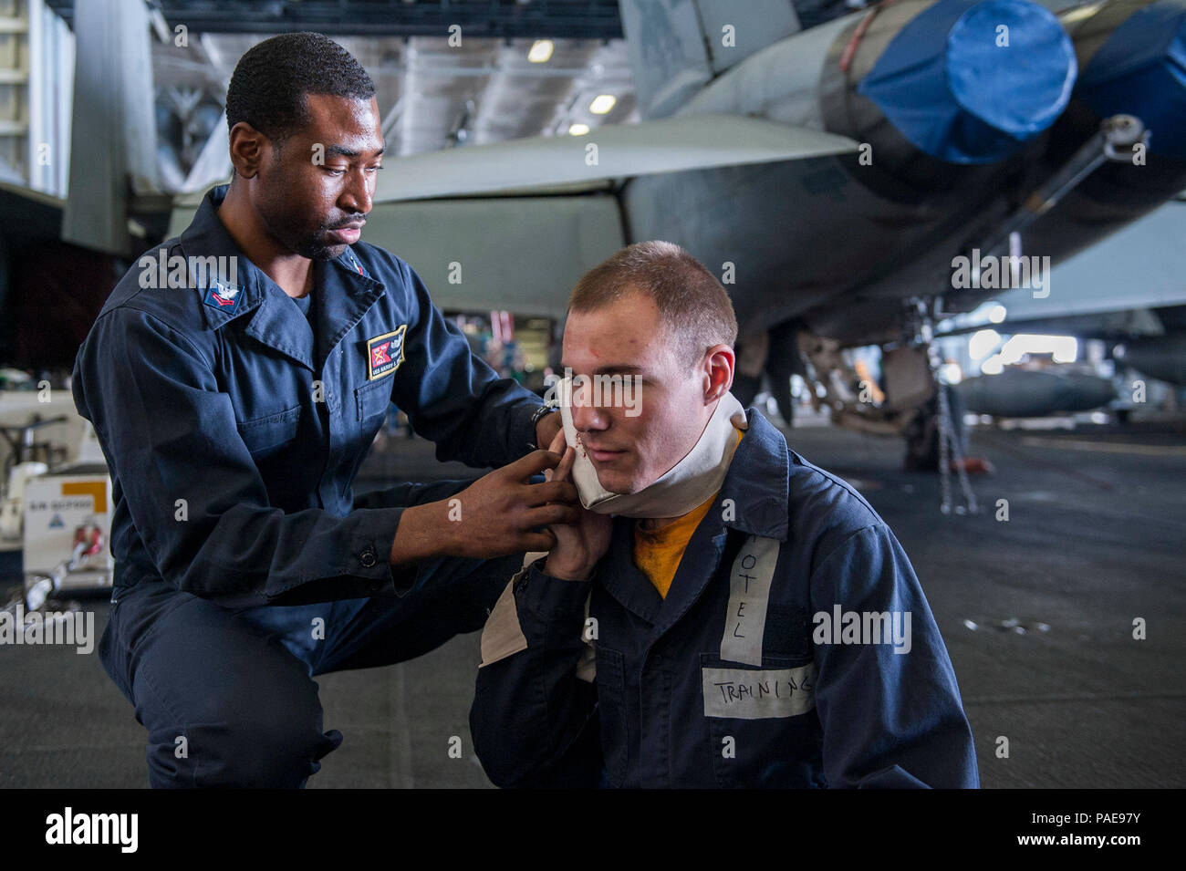 160318-N-GK939-066   ARABIAN GULF (March 18, 2016) Hospital Corpsman 2nd Class Richard Williams, left, applies pressure to a wound on a simulated casualty during a mass casualty drill in the hangar bay of aircraft carrier USS Harry S. Truman (CVN 75). Harry S. Truman Carrier Strike Group is deployed in support of Operation Inherent Resolve, maritime security operations, and theater security cooperation efforts in the U.S. 5th Fleet area of operations. (U.S. Navy photo by Mass Communication Specialist Seaman Lindsay A. Preston/Released) - Stock Image