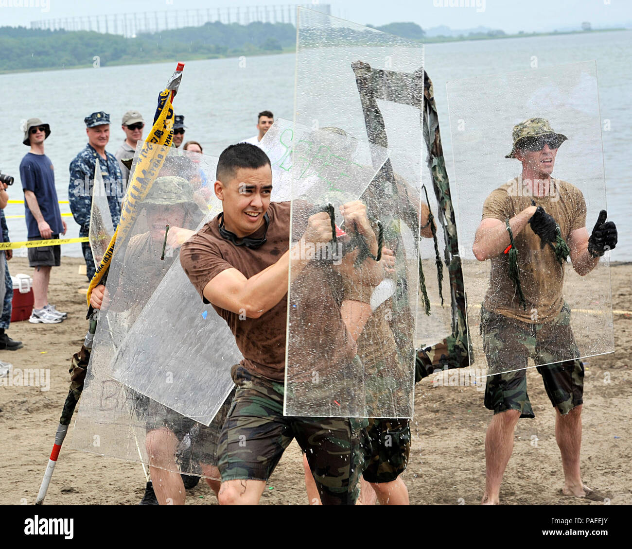 Construction Mechanic 2nd Class Nathan Breen, center, a native of Venice, Calif., and assigned to Naval Air Facility Misawa Public Works Department, shields his flag bearer from water-balloon fire during the 2013 Navy Misawa Boat Regatta, Aug. 16, 2013. Breen and his fellow Seabees took part in NAF Misawa's annual, lighthearted regatta, which calls for each team to build a vessel from non-boating materials. The teams take turns racing around Misawa Air Base's Lake Ogawara, and then must plant their vessel's flag on the opposing team's beach, while attempting to avoid water-balloon fire. Misawa - Stock Image