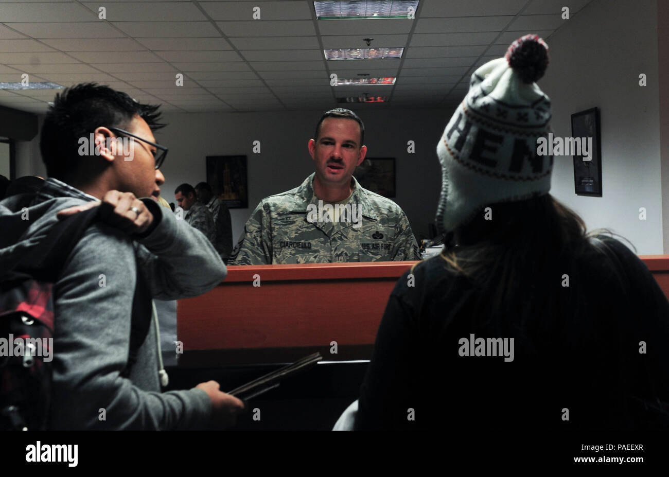 U.S. Air Force Master Sgt. Marc Ciardiello, 39th Air Base Wing legal office superintendent, speaks with U.S. Air Force Staff Sgt. Bryant Guillermo, 39th Security Forces Squadron NCO in-charge of investigation, and his wife at the processing center during the Department of State ordered departure March 30, 2016 at Incirlik Air Base, Turkey. The directed departure was conducted in close coordination with the Department of State and the Government of Turkey to ensure the safe transition of U.S. citizens from Incirlik Air Base and elsewhere in Turkey. (U.S. Air Force photo by Staff Sgt. Eboni Ream - Stock Image