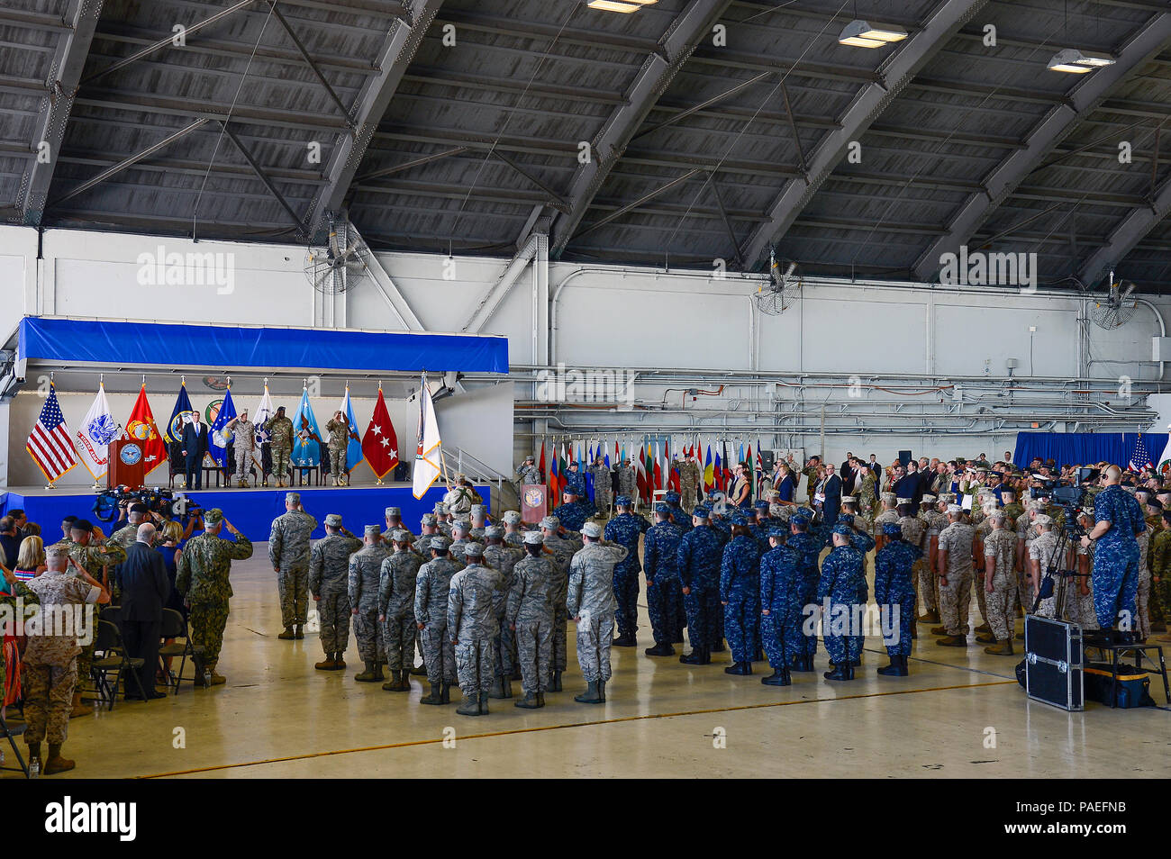 Service members render a salute during the presentation of the colors and the singing of the National Anthem at the U.S. Central Command change of command ceremony at MacDill Air Force Base, Fla., March 30, 2016. Defense Secretary Ash Carter officiated the change of command ceremony, which attracted more than 1,000 attendees, including Joint Chiefs of Staff chairman U.S. Marine Gen. Joseph F. Dunford, Central Command's component commanders, community leaders and senior coalition representatives. (U.S. Air Force photo by Senior Airman Ned T. Johnston) Stock Photo