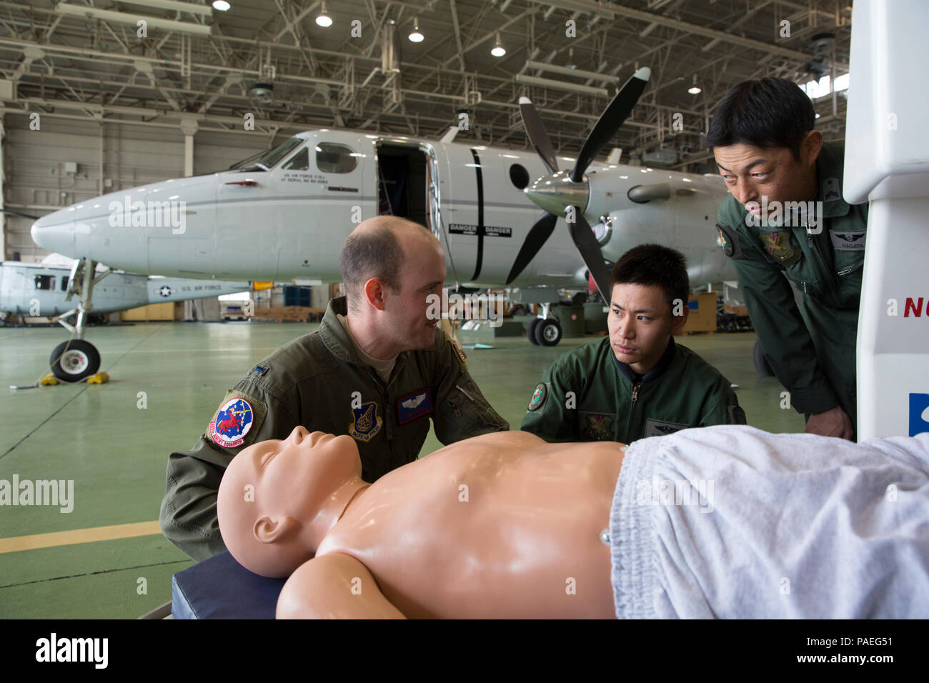 (Left to right) U.S. Air Force 1st Lt. Anthony Pergola, 459th Airlift Squadron C-12 pilot, talks about an Aeromedical Evacuation Spectrum Bed to Japan Air Self-Defense Capt. Daiki Ishihara, 402nd Squadron C-1 pilot, and JASDF Tech. Sgt. Shoji Nagata, 402nd Squadron C-1, U-4 loadmaster, at Yokota Air Base, Japan, March 30, 2016. 459 AS members demonstrated Aeromedical Evacuation procedures of a C-12 Huron to JASDF members to improve the working relationship between JASDF and USAF. (U.S. Air Force photo by Yasuo Osakabe/Released) Stock Photo