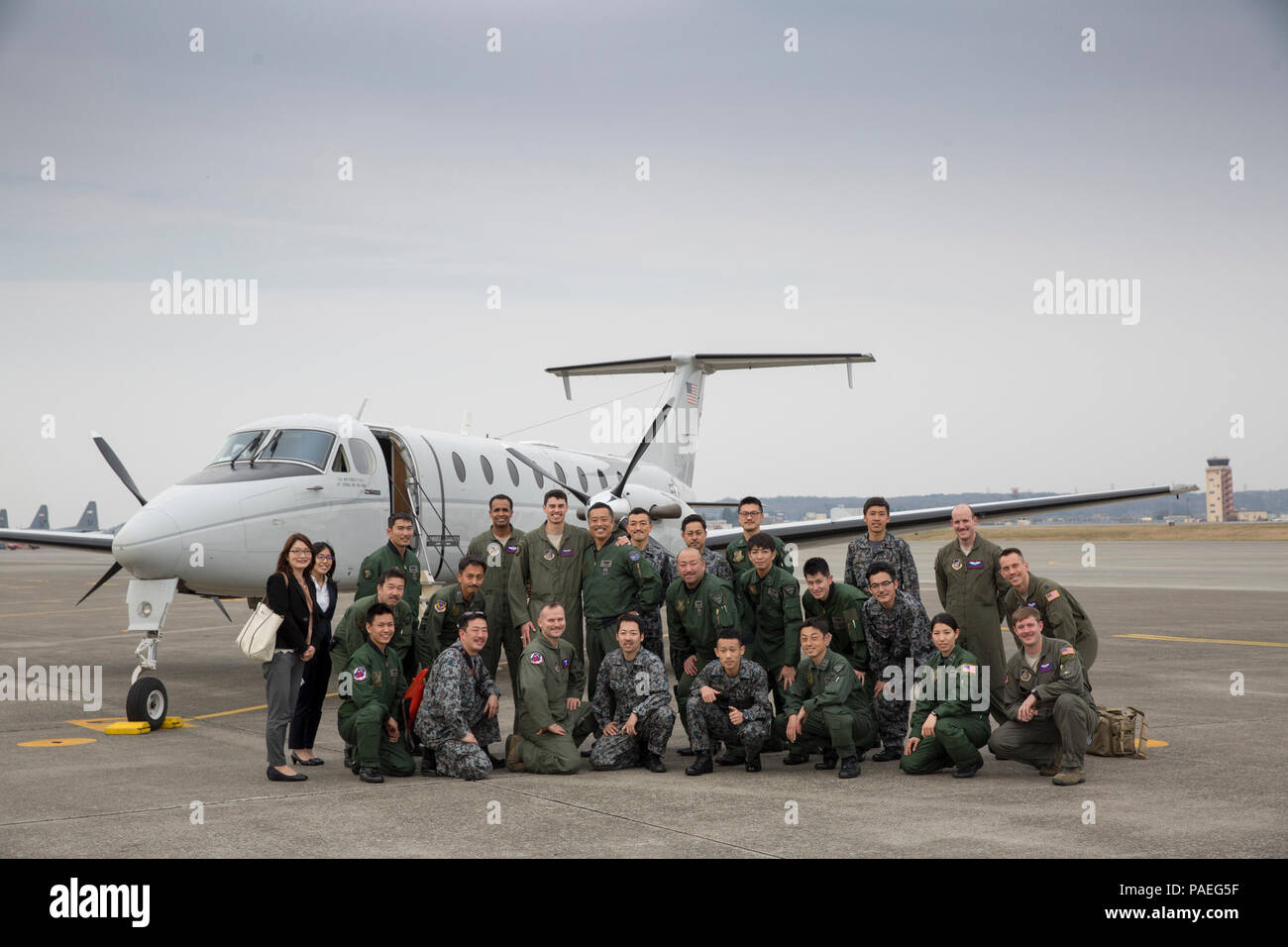 Crew members with the Japan Air Self-Defense Force and U.S. Air Force 459th Airlift Squadron pose for a photo by a USAF C-12 Huron at Yokota Air Base, Japan, March 30, 2016. 459 AS hosted familiarization flight for members from the 402 SQ to introduce Aeromedical Evacuation operations and demonstrate operating the AE Spectrum Bed. (U.S. Air Force photo by Yasuo Osakabe/Released) Stock Photo