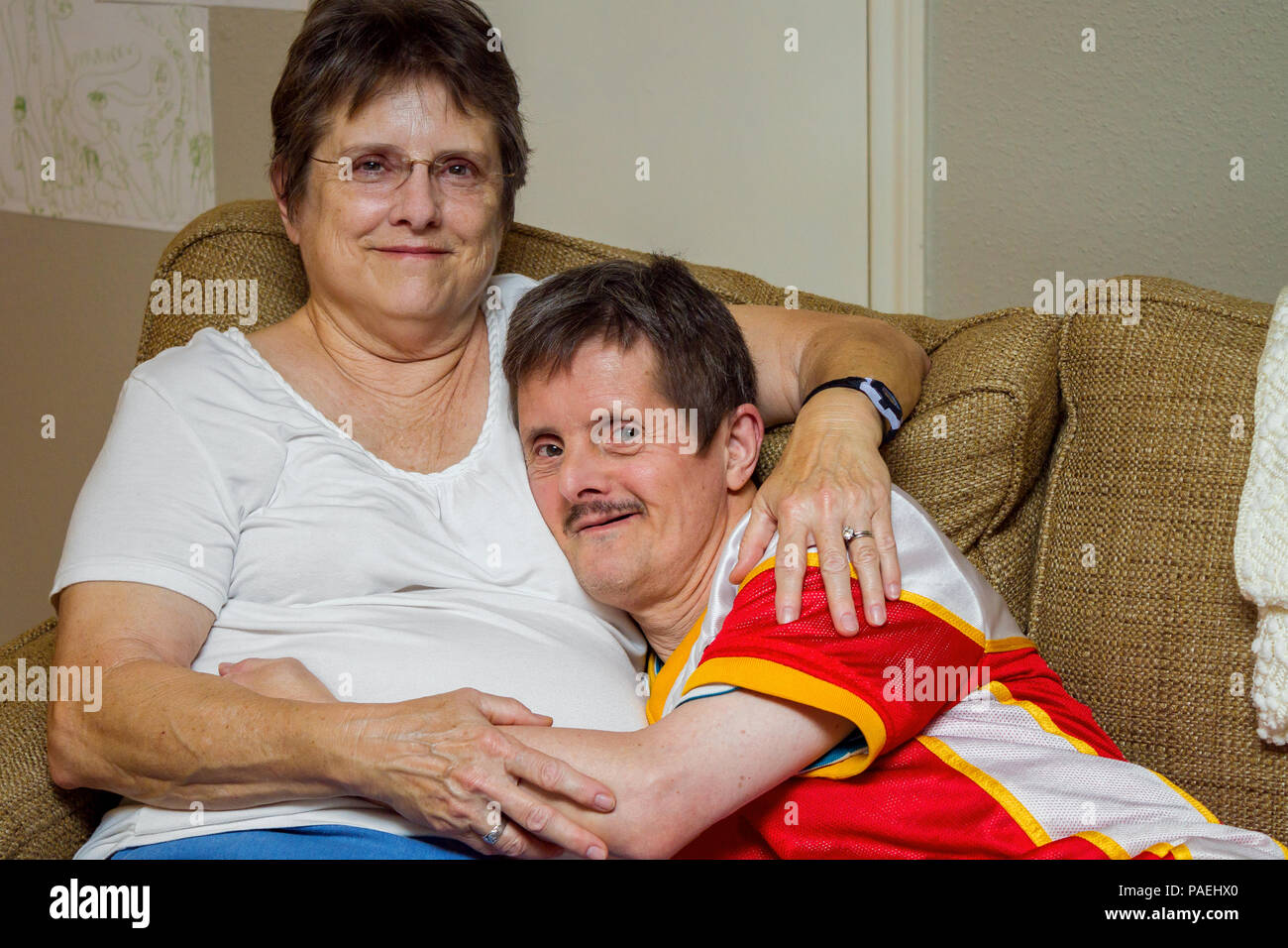 An older man with Downs Syndrome, hugs his older sister as they sit on a couch. The woman looks tired, the man looks mischeivious.  He is about to tic - Stock Image