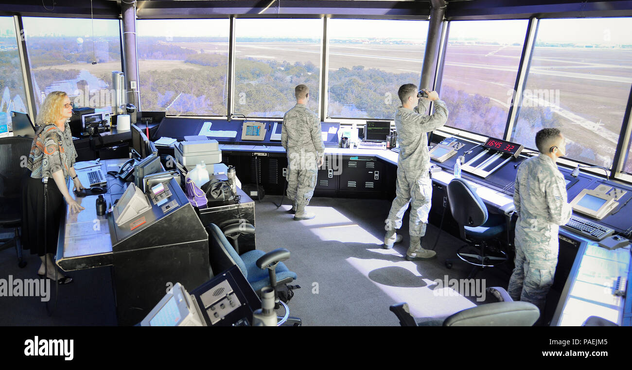 Mrs. Angela Hull, a watch supervisor at MacDill Air Force Base's air traffic control tower, watches over controllers as they communicate with inbound and outbound aircraft at MacDill Air Force Base, Fla., March 1, 2016. Hull, a retired 21-year senior master sergeant, continues to serve today sharing the knowledge and experience she gained from her long career. (U.S. Air Force photo by Senior Airman Ned T. Johnston) Stock Photo