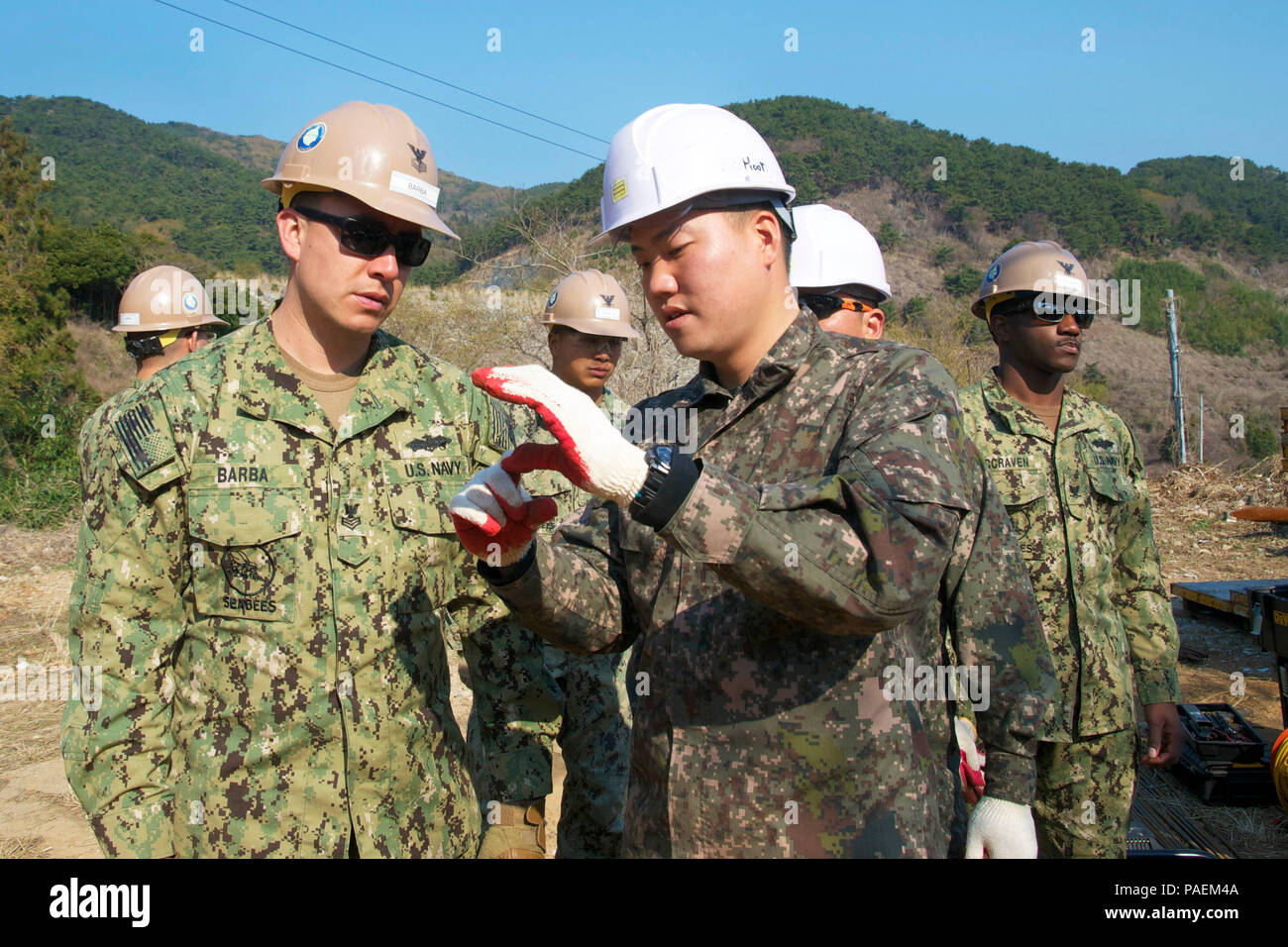 160327-N-NE195-001  YOKIJIDO ISLAND, Republic of Korea (Mar. 27, 2016) - Prior to the construction of a road project on Yokjido Island, Builder 1st Class Oscar Barba, assigned to Naval Mobile Construction Battalion (NMCB) 4 and an engineer from the Republic of Korea (ROK) Construction Battalion, discuss the difference between the metric system and the U.S. customary unit of measurement during Exercise Foal Eagle, Mar. 27. The paved road will shorten the distance of travel to connect 2,000 locals more efficiently to exchange goods, services and improve economical growth. Foal Eagle is a series  - Stock Image