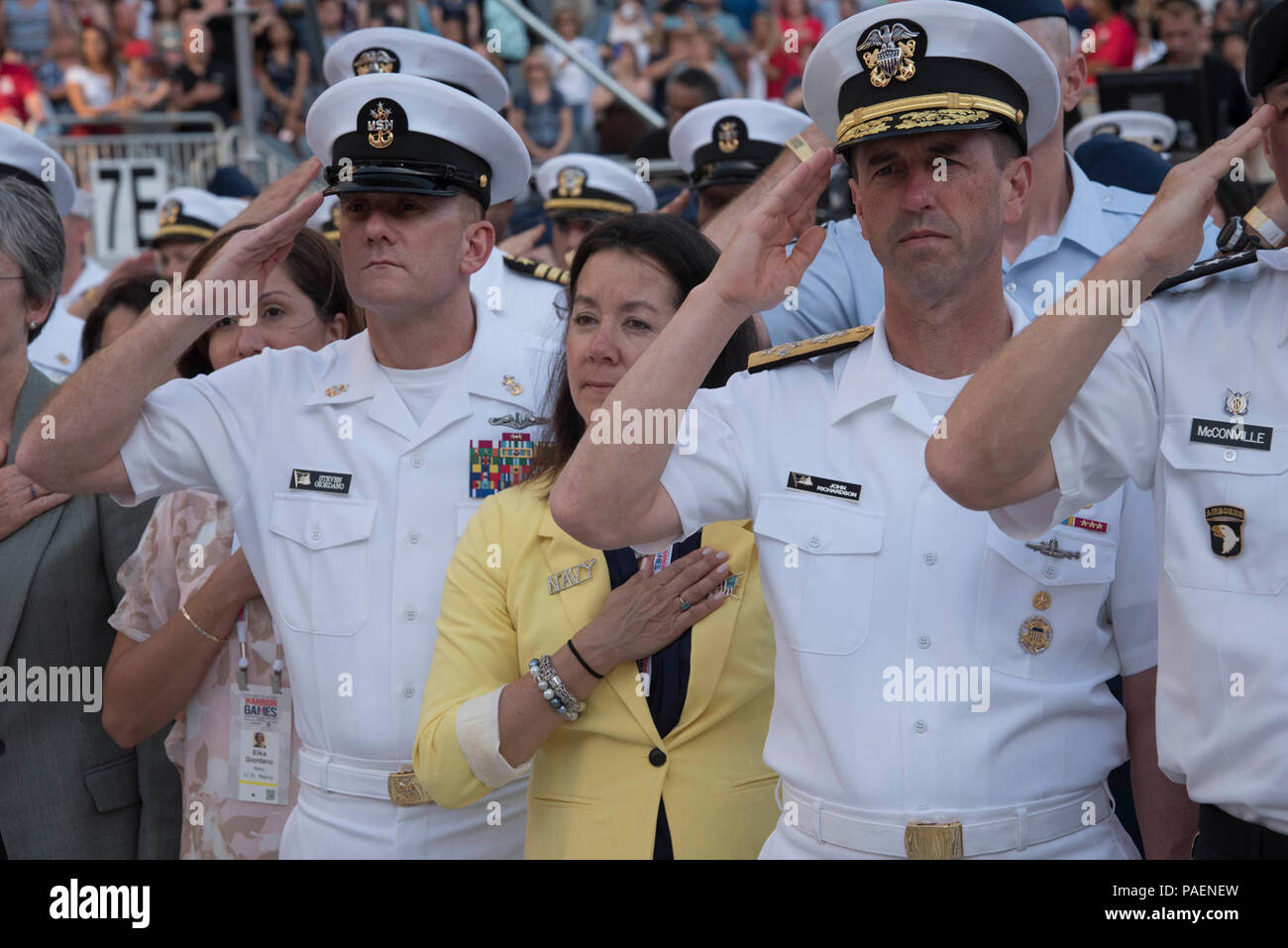 (July 1, 2017) Chief of Naval Operations Adm. John Richardson, Master Chief Petty Officer of the Navy (MCPON) Steven Giordano, and their spouses salute during the National Anthem at the Department of Defense (DoD) Warrior Games' opening ceremony at Soldier Field in Chicago. The Warrior Games run until July 8. The athletes will test their abilities in seven adaptive sports: archery, cycling, track and field, shooting, sitting volleyball, swimming and wheelchair basketball. Team Navy is comprised of athletes from Navy Wounded Warrior - Safe Harbor, the Navy's sole organization for coordinating t - Stock Image