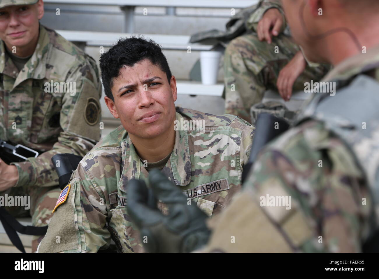 Staff Sgt. Gretchen Martinez from the Fires Center of Excellence talks to her fellow competitors during the Range event for the TRADOC Best Warrior Competition, Fort Gordon, Georgia, July 17, 2018. The Best Warrior Competition recognizes TRADOC NCOs and Soldiers who demonstrate commitment to the Army Values, embody the Warrior Ethos, and represent the force of the future by testing them with physical fitness assessments, written exams, urban warfare simulations, and other warrior tasks and battle drills. (U.S. Army photo by Pfc. Caeli Morris) Stock Photo