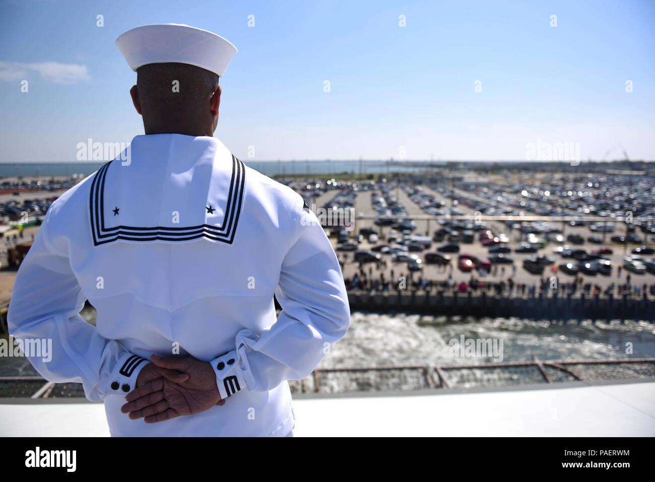 NORFOLK (April 11, 2018) Personnel Specialist 3rd Class Anthony White mans the rails aboard the aircraft carrier USS Harry S. Truman (CVN 75) during the ship's departure from homeport. Harry S. Truman is underway as the flagship for the Harry S. Truman Carrier Strike Group which includes; guided-missile cruiser USS Normandy (CG-60), and guided-missile destroyers USS Arleigh Burke (DDG-51), USS Bulkeley (DDG-84), USS Farragut (DDG-99), USS Forrest Sherman (DDG-98), USS The Sullivans (DDG-68), USS Winston S. Churchill (DDG-81) for a regularly scheduled deployment. Stock Photo