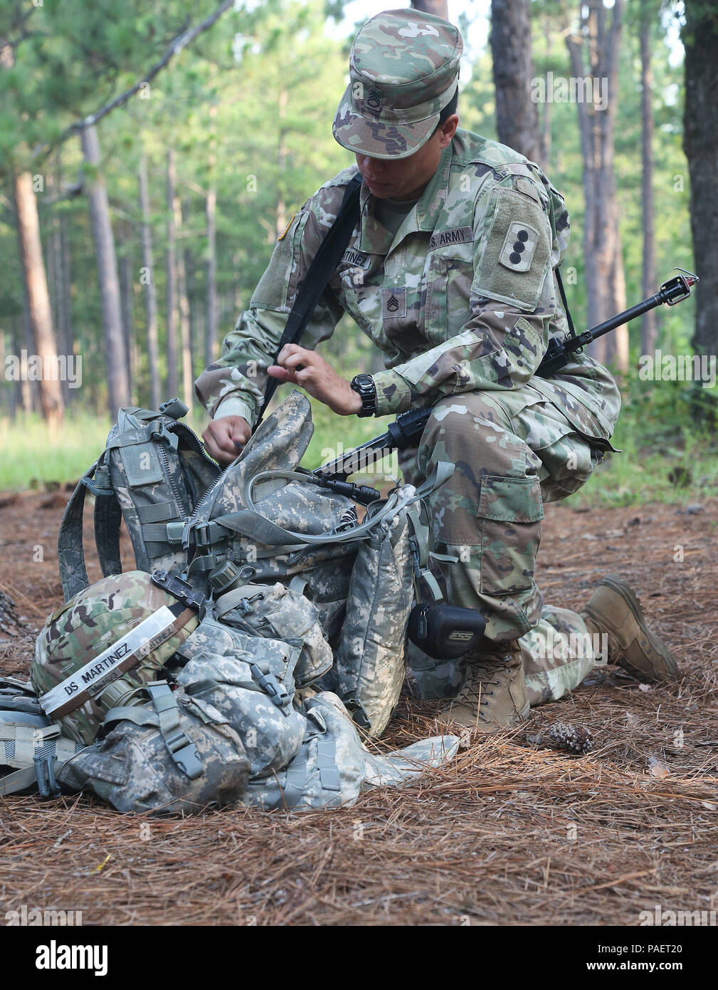 Staff Sgt. Gretchen Martinez from the Fires Center of Excellence gets her equipement ready to go through the react to direct/indirect fire lanes during the TRADOC Best Warrior Competition, Fort Gordon, Georgia, July 18, 2018. The Best Warrior Competition recognizes TRADOC NCOs and Soldiers who demonstrate commitment to the Army Values, embody the Warrior Ethos, and represent the force of the future by testing them with physical fitness assessments, written exams, urban warfare simulations, and other warrior tasks and battle drills. (U.S. Army photo by Pfc. Caeli Morris) Stock Photo